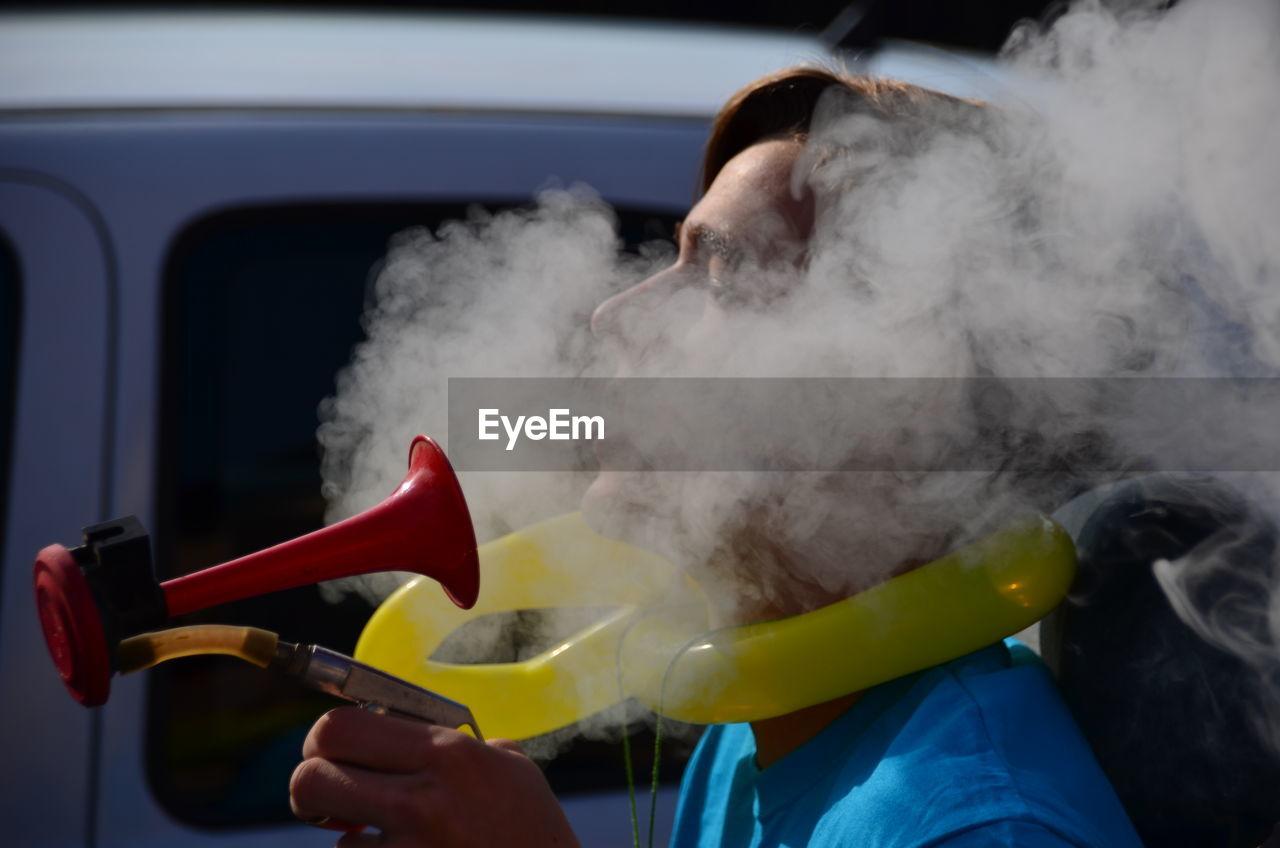 Close-up of man smoking outdoors