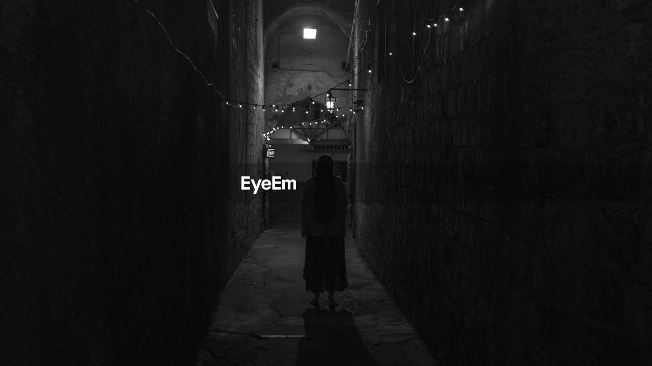 Rear view of woman standing in alley at night
