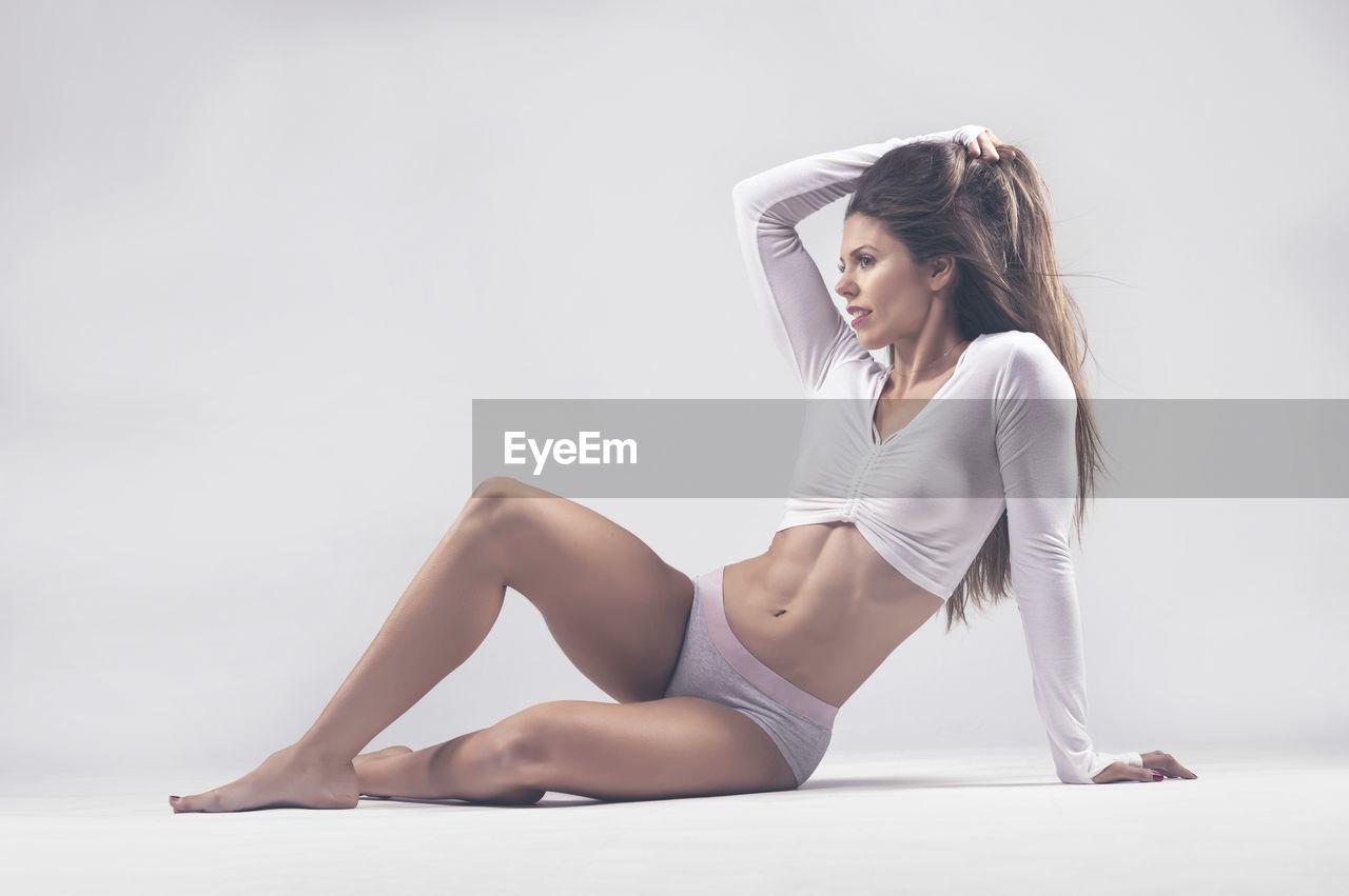 Thoughtful muscular female athlete sitting against white background
