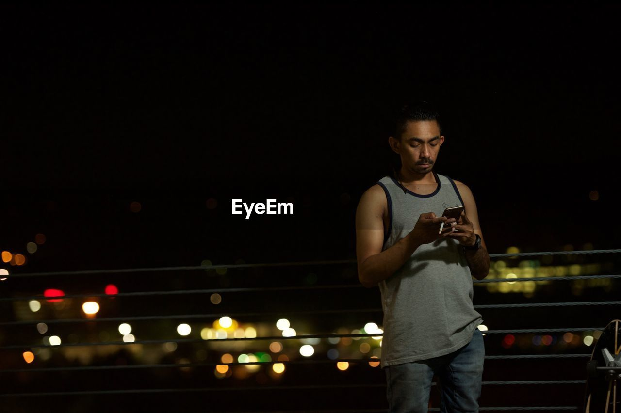 night, illuminated, one person, real people, connection, standing, casual clothing, holding, young adult, wireless technology, leisure activity, mobile phone, lifestyles, outdoors