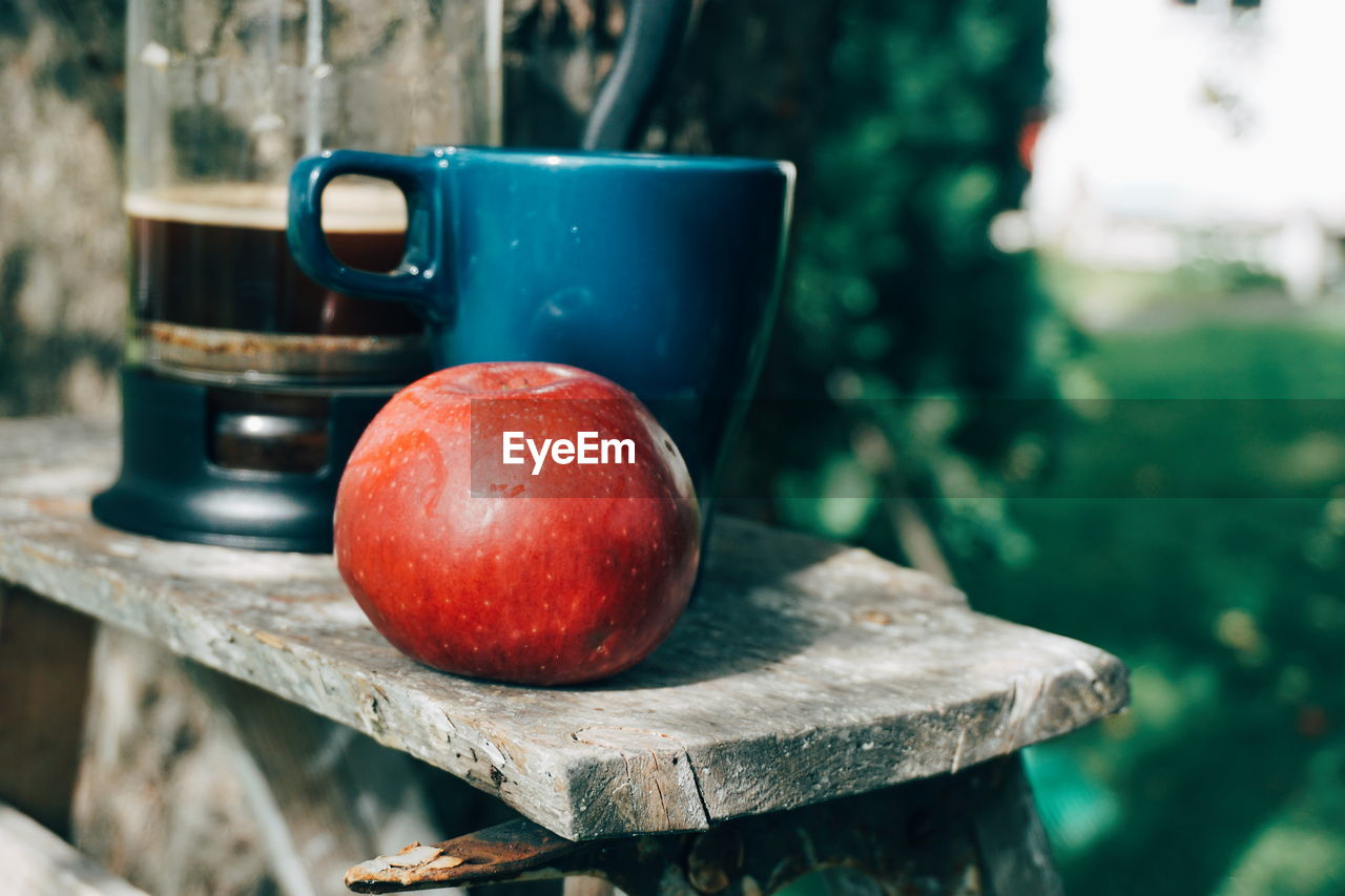 Close-Up Of Apple And Mug On Table