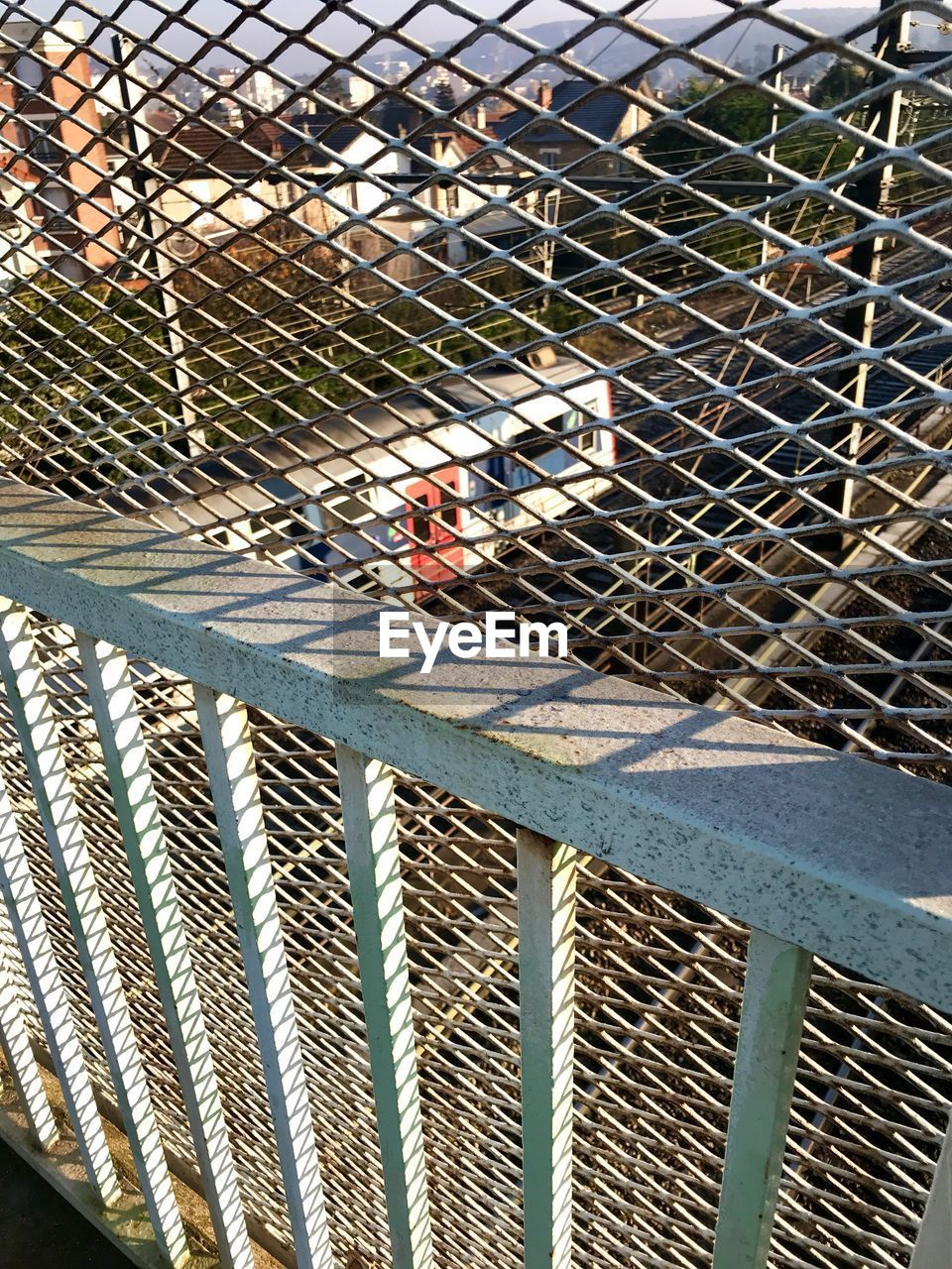 fence, barrier, boundary, metal, safety, day, protection, chainlink fence, security, sunlight, real people, transportation, one person, outdoors, construction industry, nature, built structure, men, road