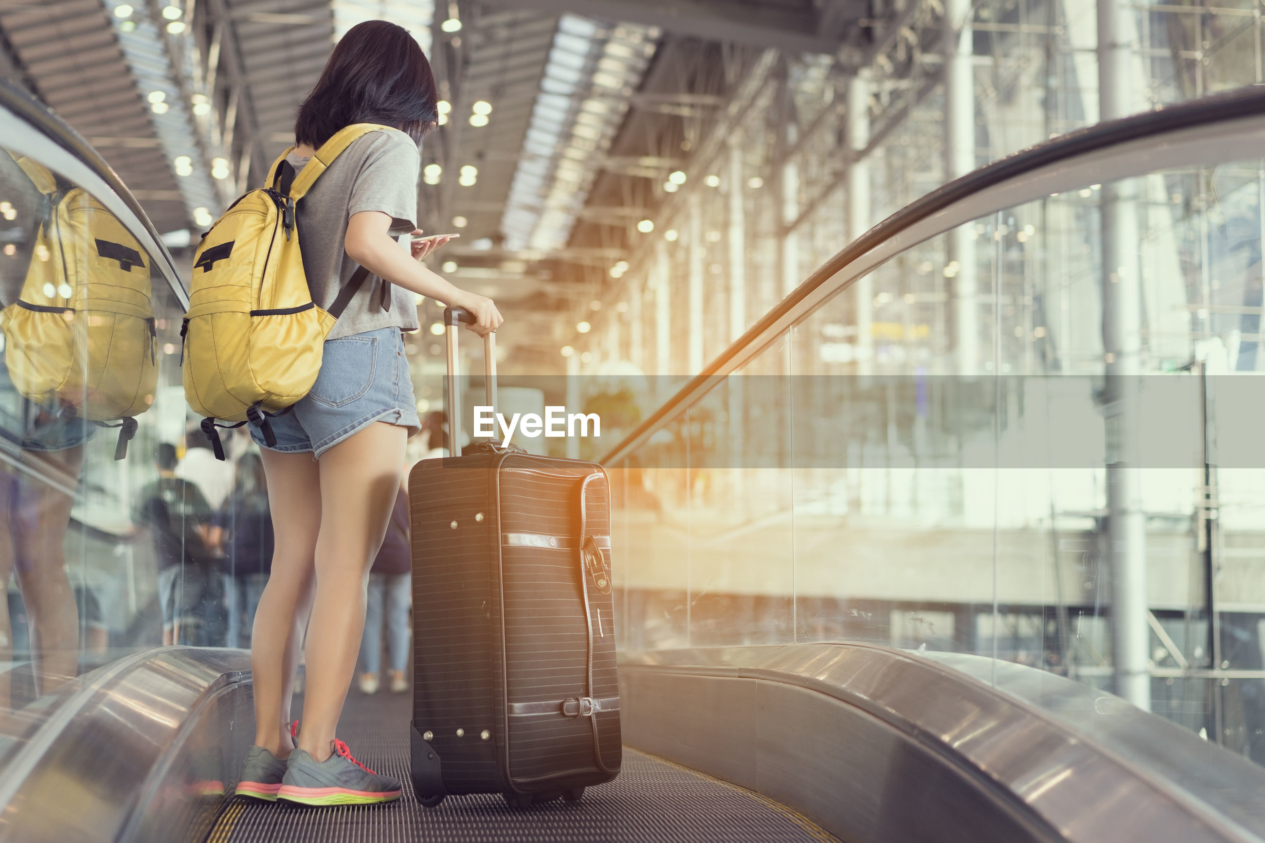 Woman carrying luggage on moving walkway in airport