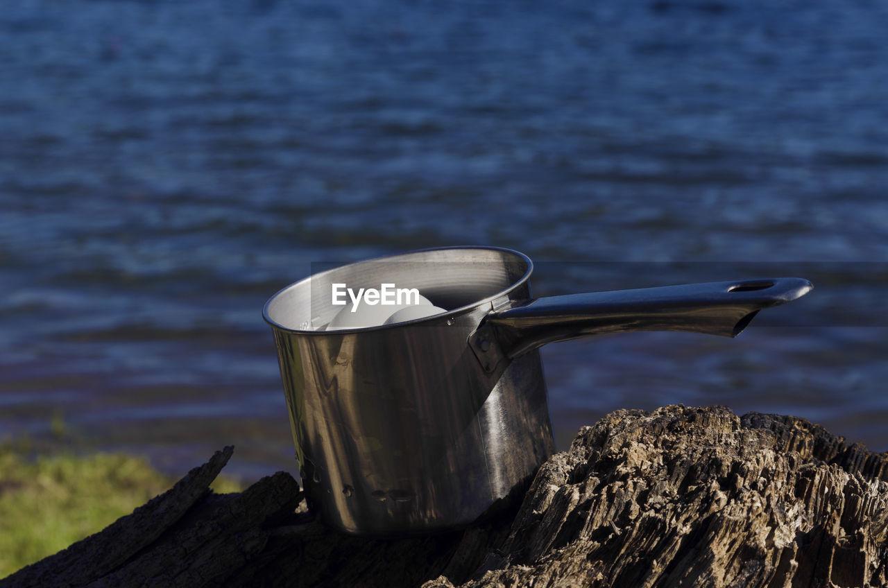 Eggs in utensil on wood by lake