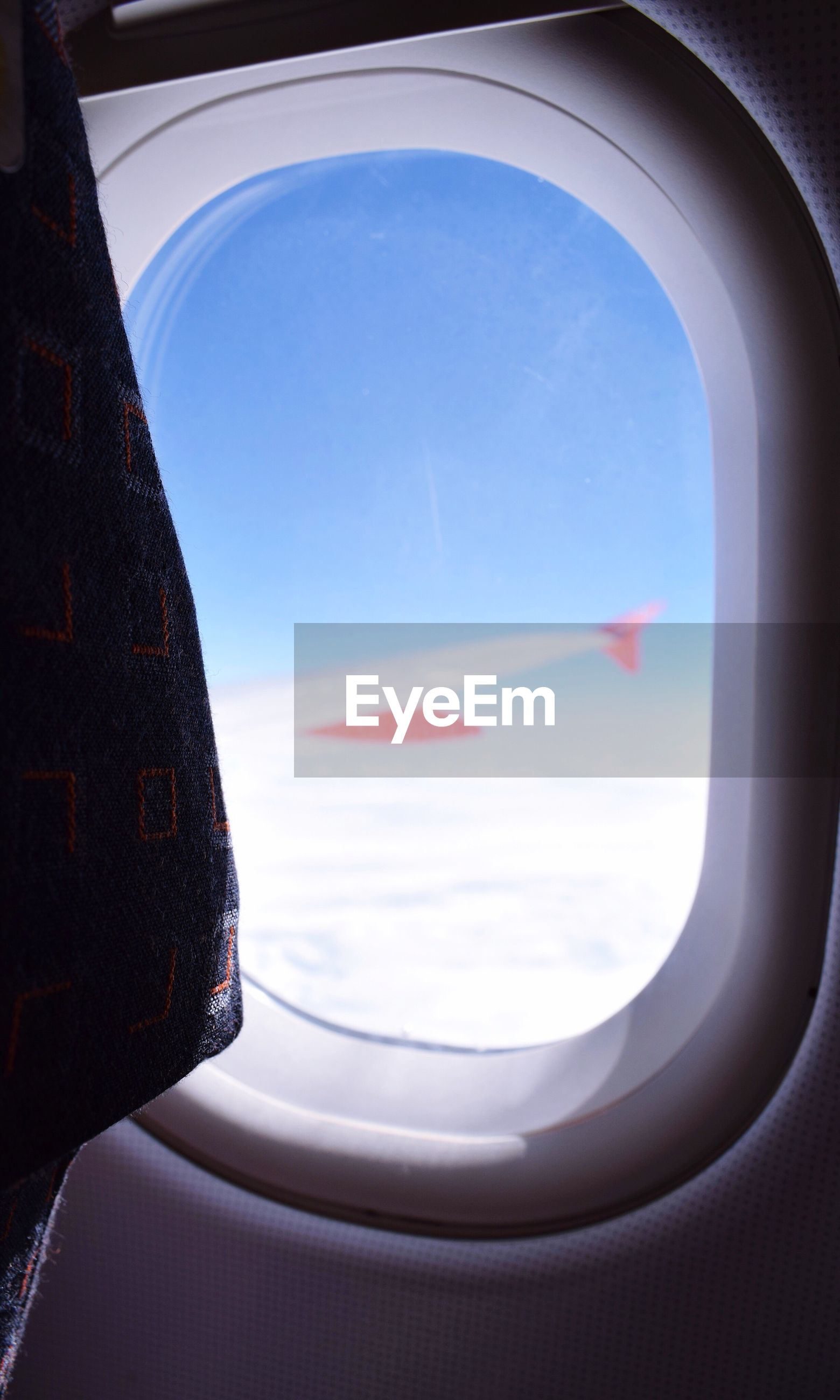 CLOSE-UP OF AIRPLANE WING AGAINST SKY SEEN FROM WINDOW