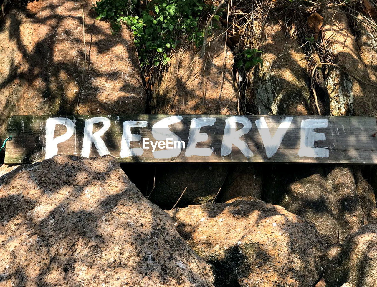 text, communication, western script, day, sunlight, capital letter, no people, sign, nature, shadow, plant, tree, single word, outdoors, graffiti, writing, information, solid, rock, wall, message