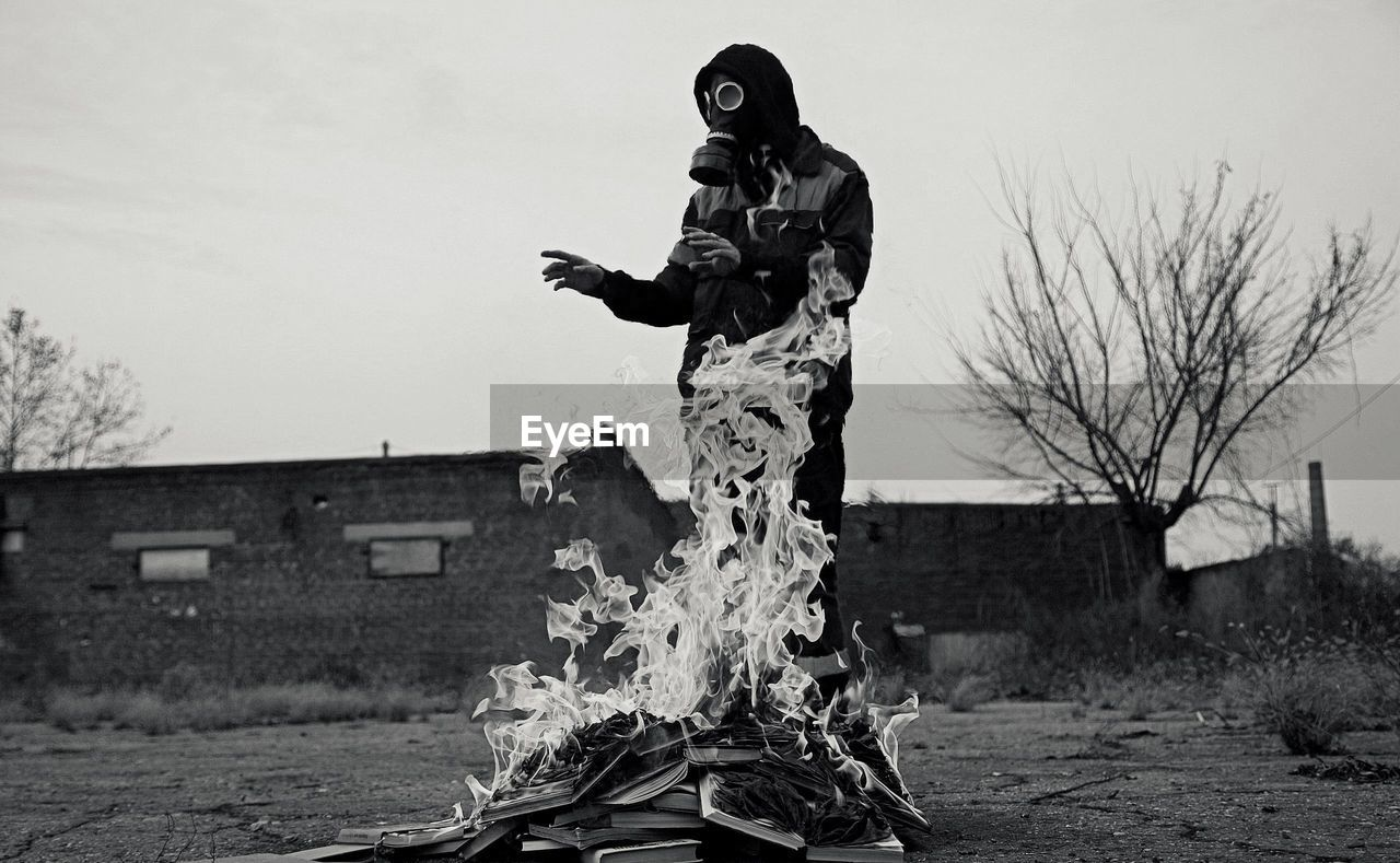 Person wearing gas mask while standing by fire on land against sky