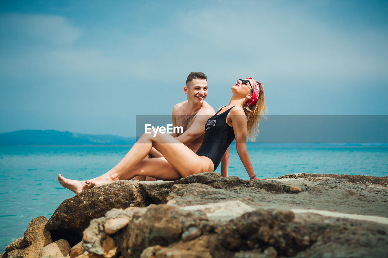 water, sea, two people, sky, young adult, young women, leisure activity, lifestyles, real people, nature, women, beauty in nature, togetherness, solid, adult, sitting, land, rock, rock - object, couple - relationship, fashion, horizon over water, outdoors