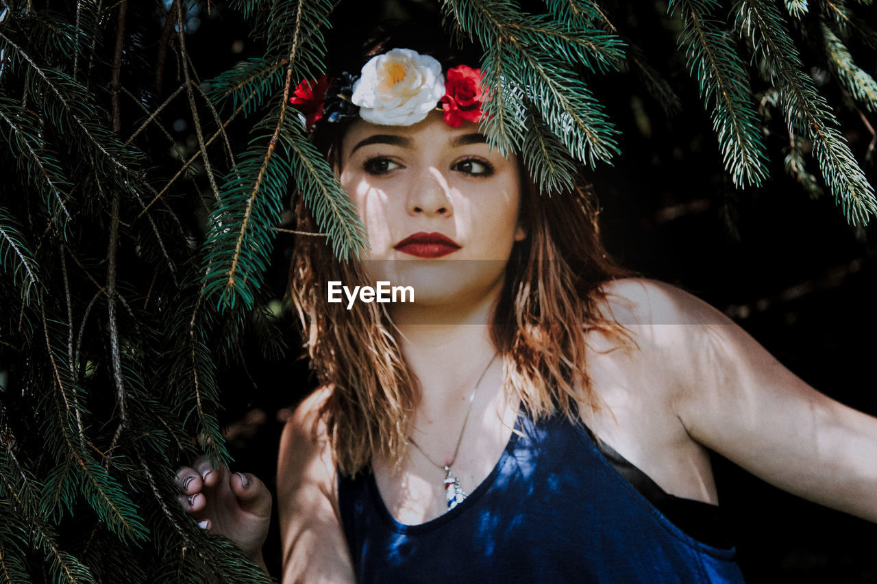 Beautiful Young Woman Wearing Flowers Amidst Branches