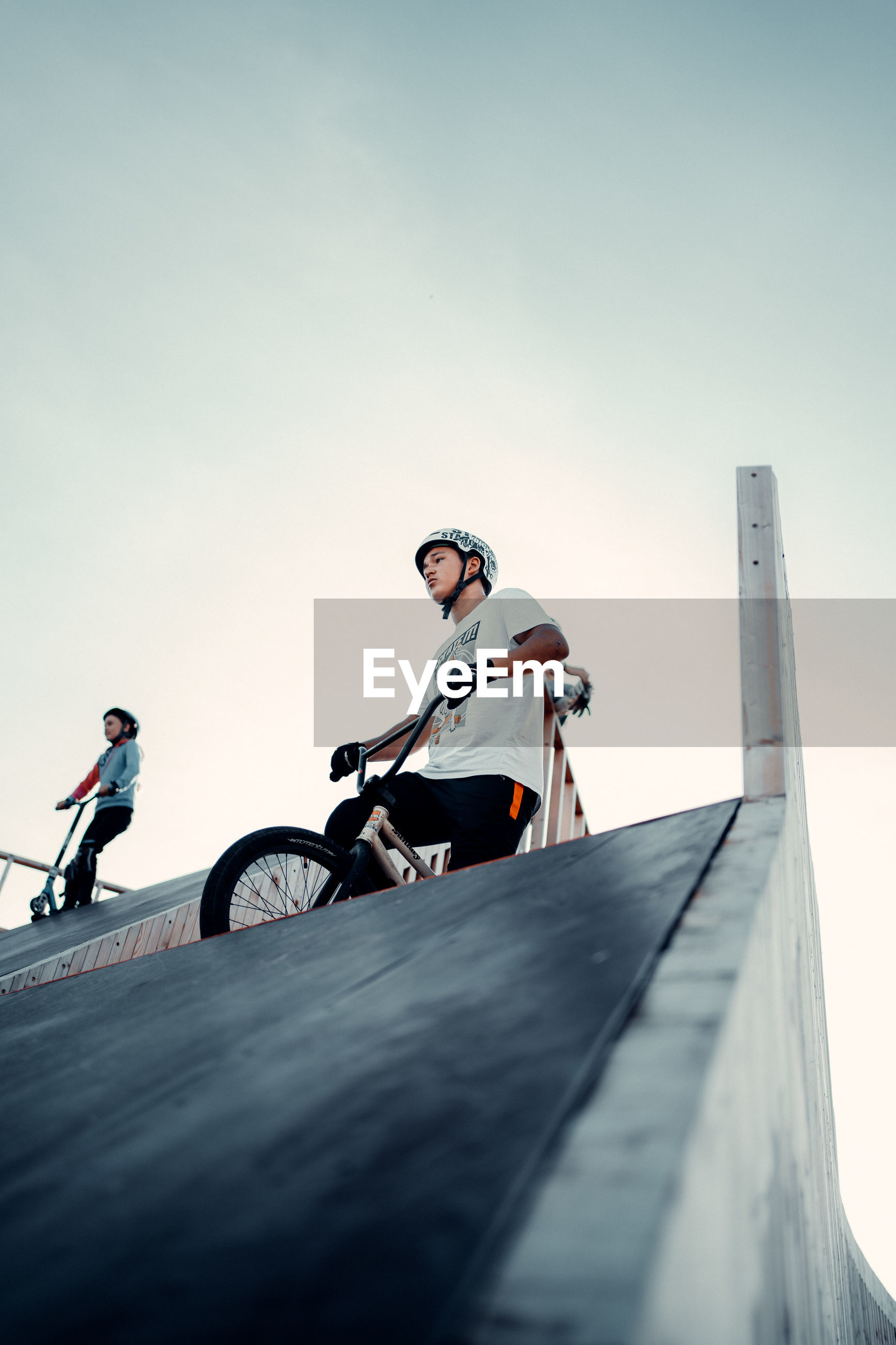 LOW ANGLE VIEW OF MAN RIDING BICYCLE ON ROAD