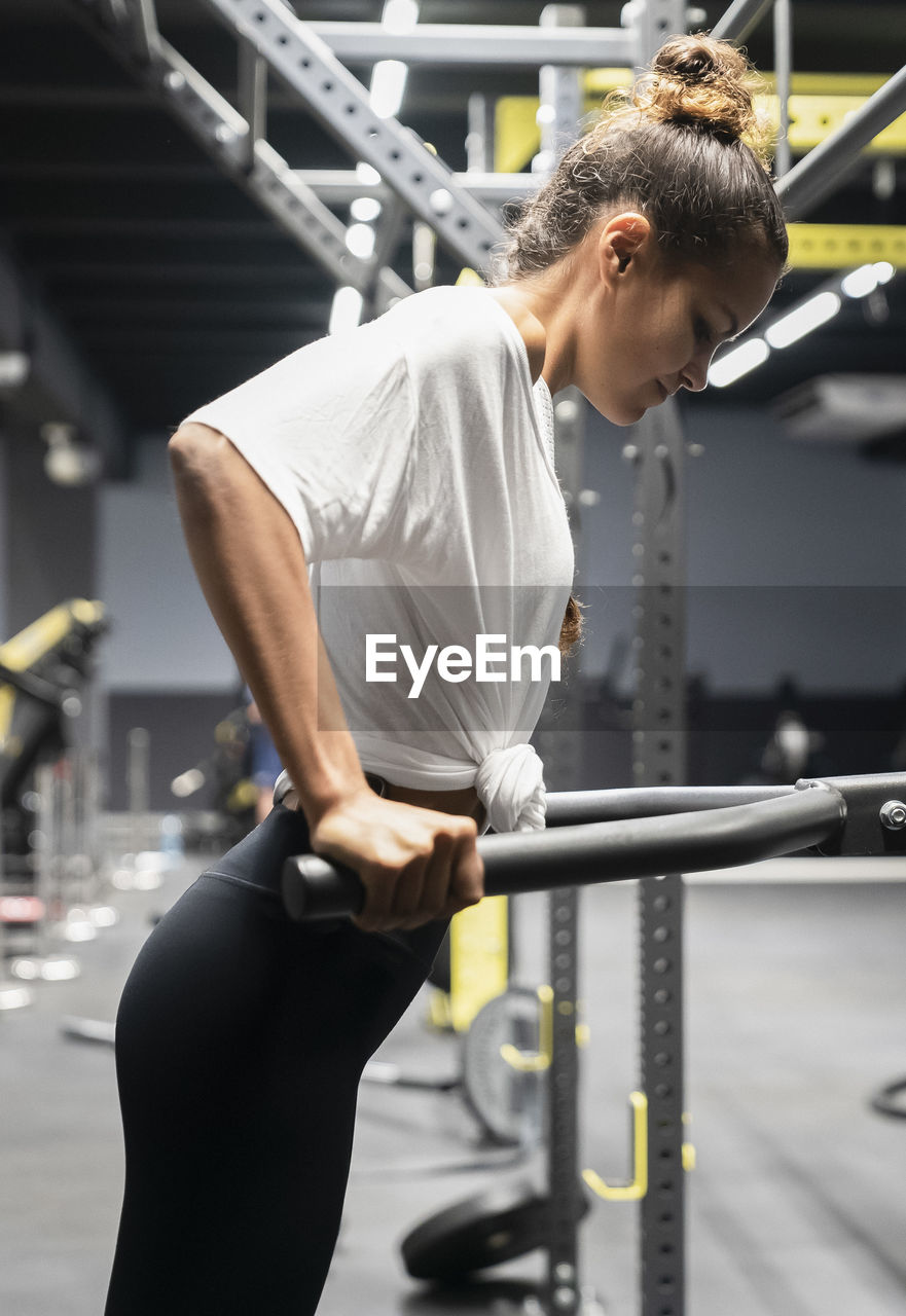 one person, exercising, healthy lifestyle, gym, real people, sport, strength, lifestyles, sports training, sports clothing, muscular build, focus on foreground, three quarter length, indoors, young adult, vitality, wellbeing, clothing, health club, effort, body conscious, physical activity, exercise machine, weight training