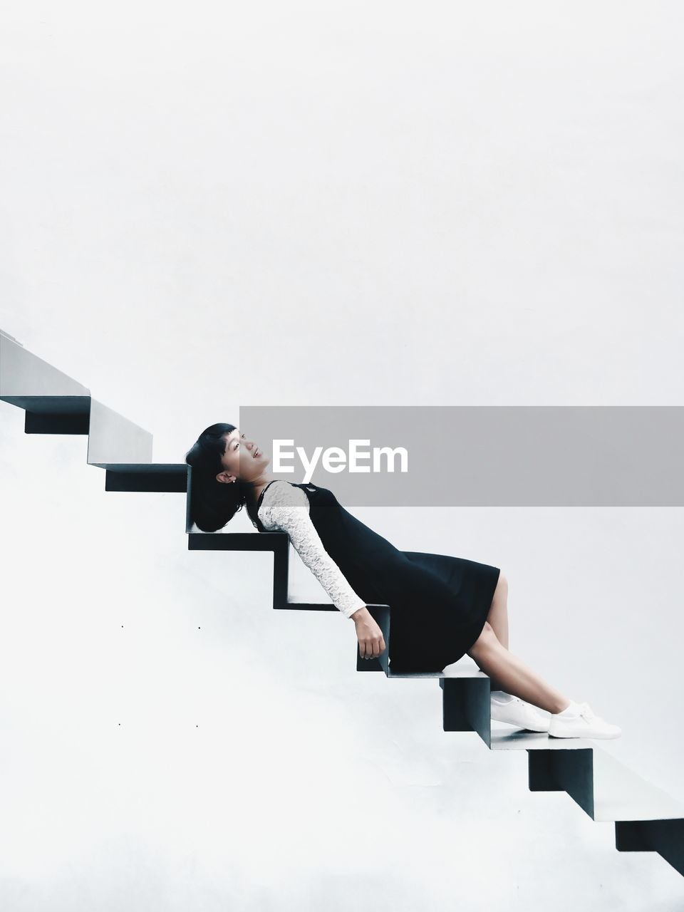 Young Woman Lying On Steps Against White Background