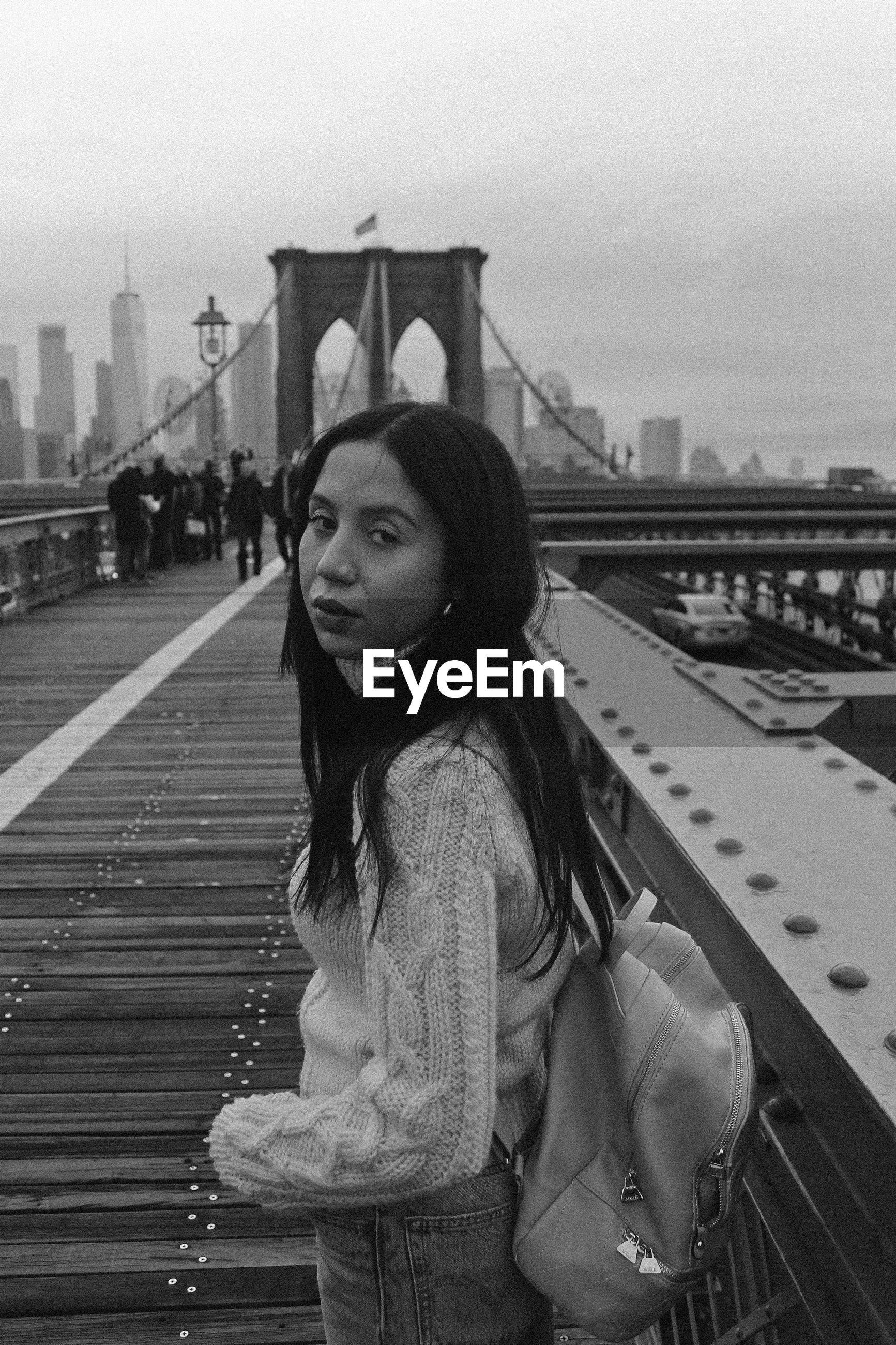 Portrait of backpack woman standing on brooklyn bridge