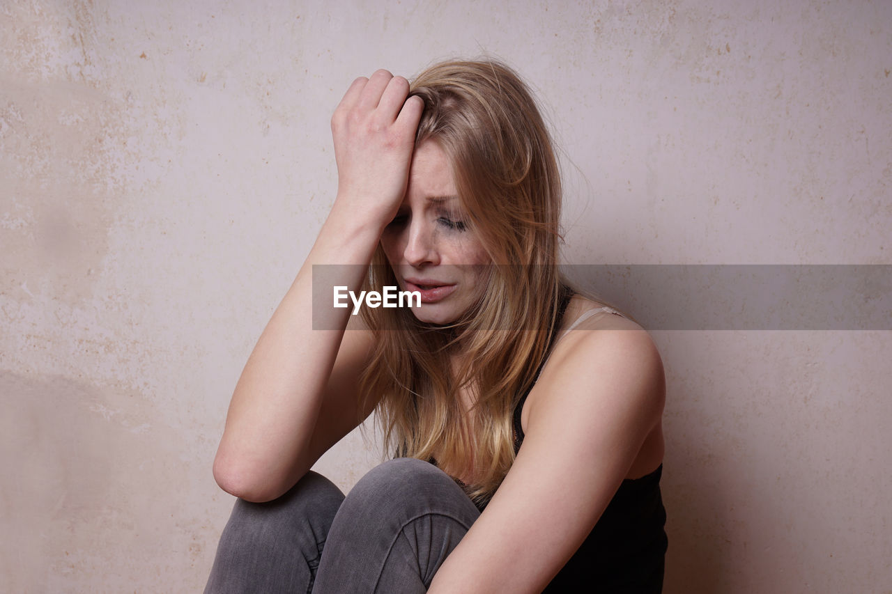 Crying Young Woman Sitting Against Wall