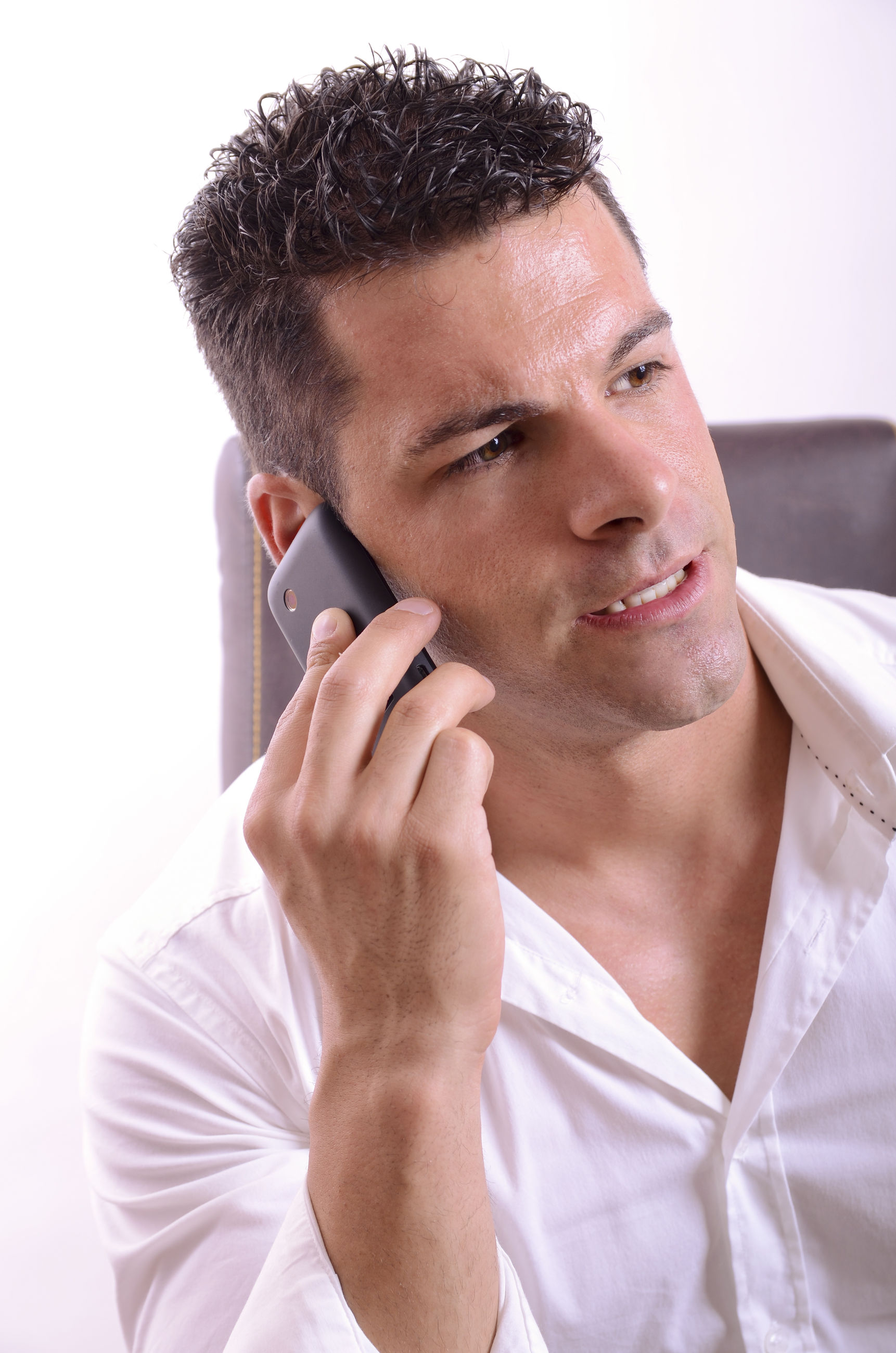 Businessman answering smart phone while looking away in office