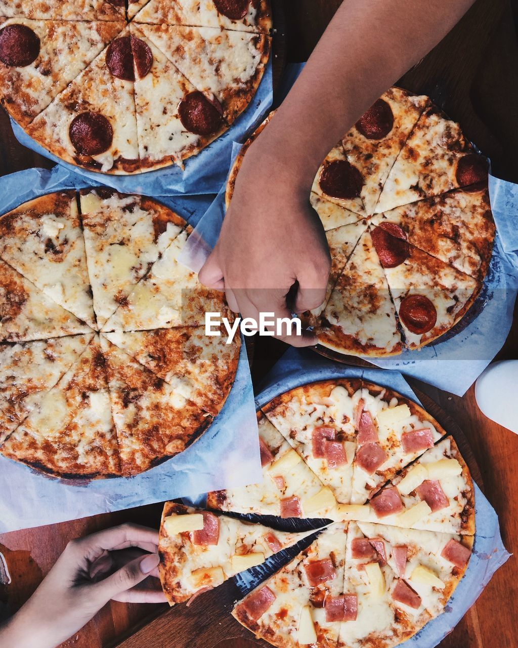 Cropped Image Of Hands Holding Pizza On Table