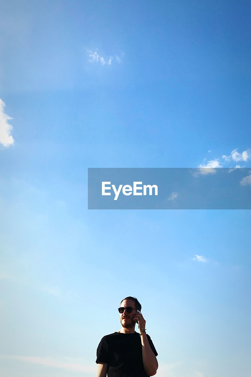 sky, lifestyles, one person, real people, young adult, leisure activity, low angle view, front view, day, portrait, cloud - sky, standing, headshot, nature, young men, sunlight, young women, outdoors, blue