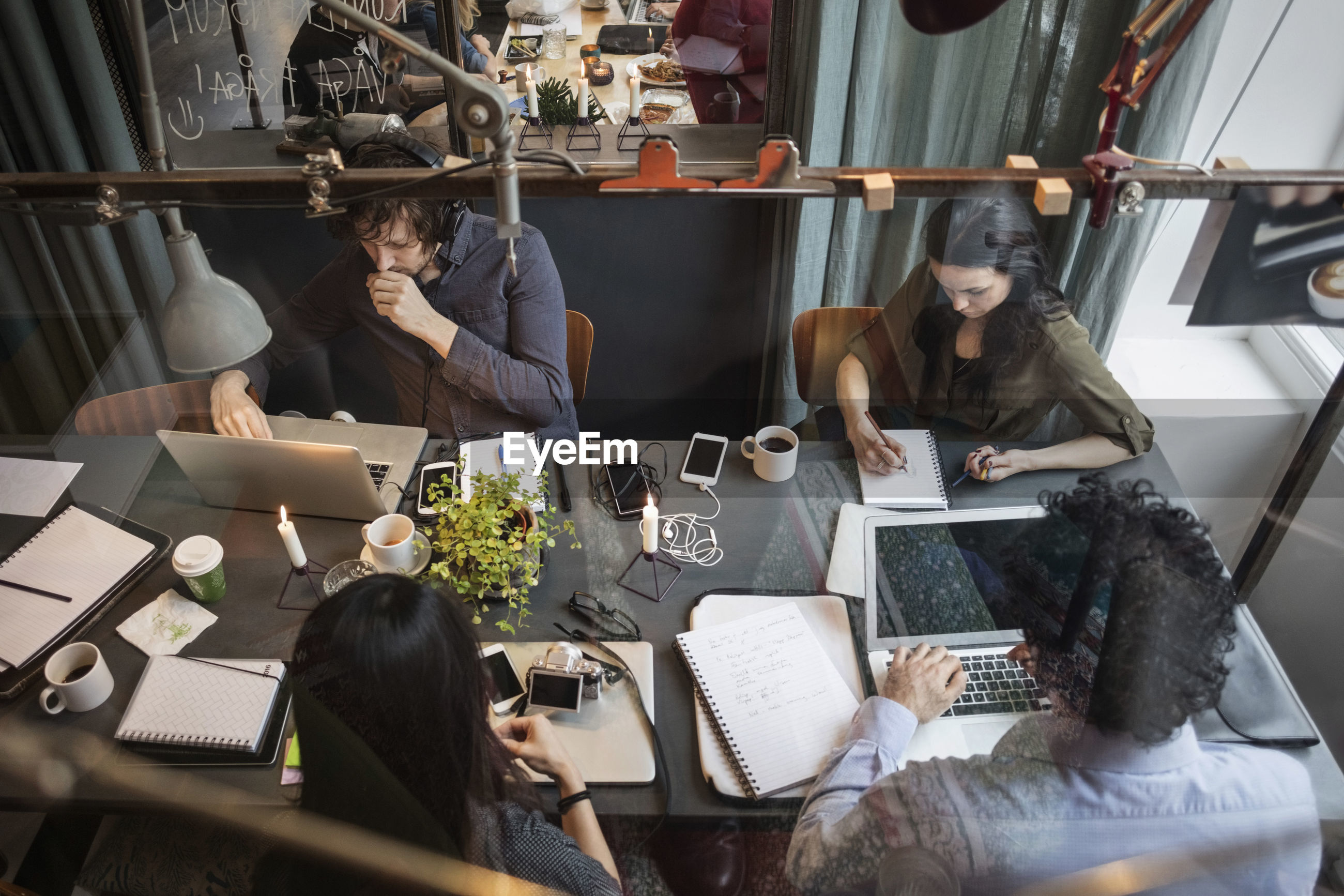 High angle view of creative team working at table in office seen through glass