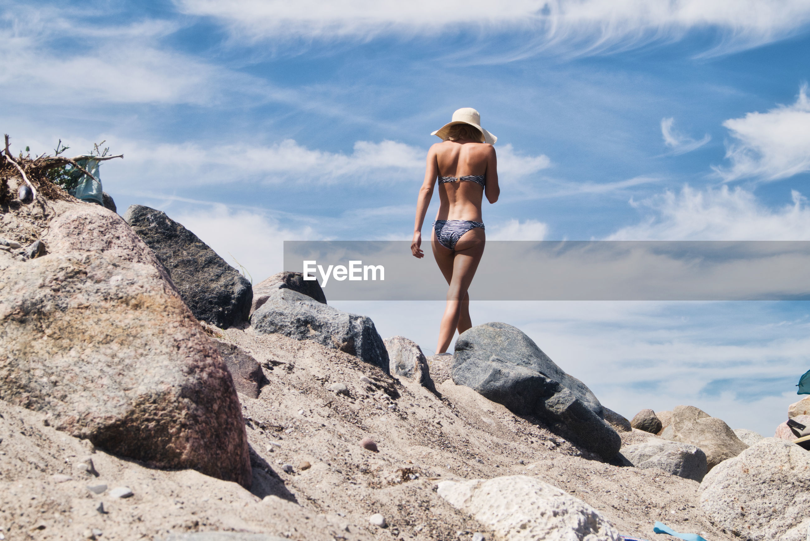 Rear view of woman wearing bikini while walking on land against sky
