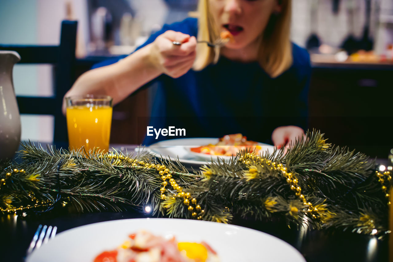 Midsection Of Woman Eating Food At Home During Christmas