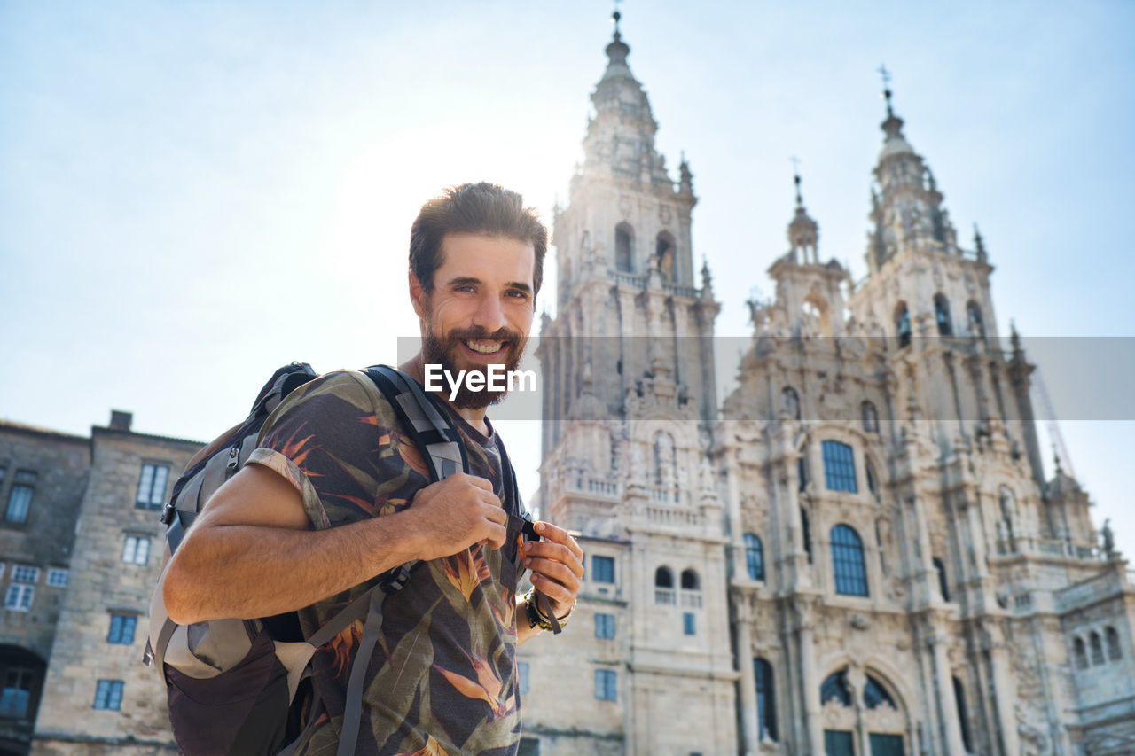 Portrait of smiling man standing against cathedral in city