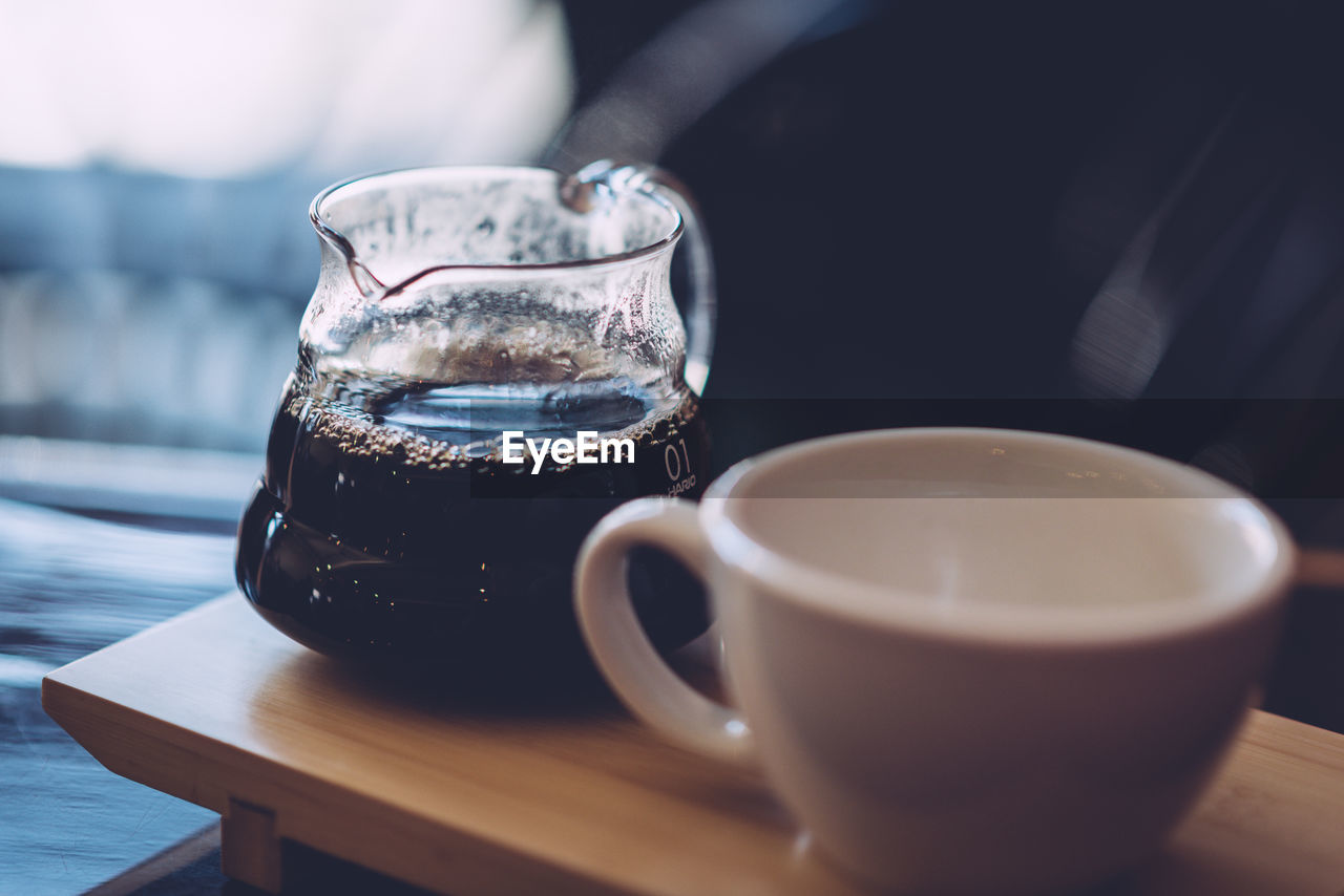Close-Up Of Black Coffee In Jug By Cup On Table