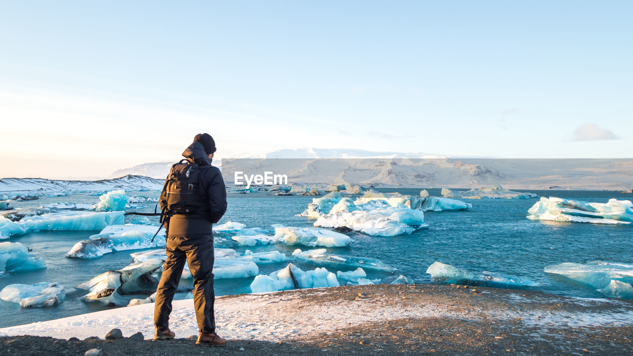 Rear view of man looking at ice bergs on sea