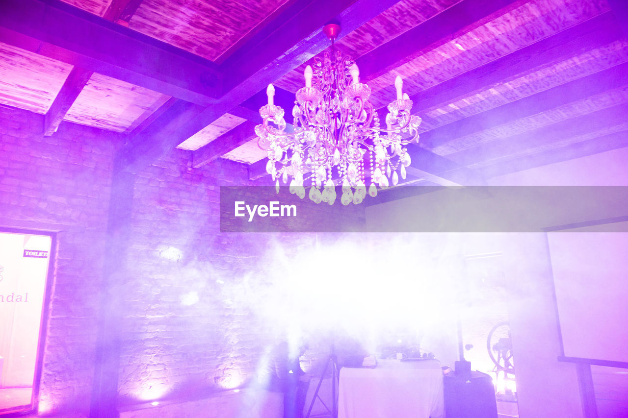 illuminated, lighting equipment, indoors, ceiling, music, purple, arts culture and entertainment, light, low angle view, hanging, flowering plant, event, flower, decoration, chandelier, no people, night, nightlife, built structure, stage