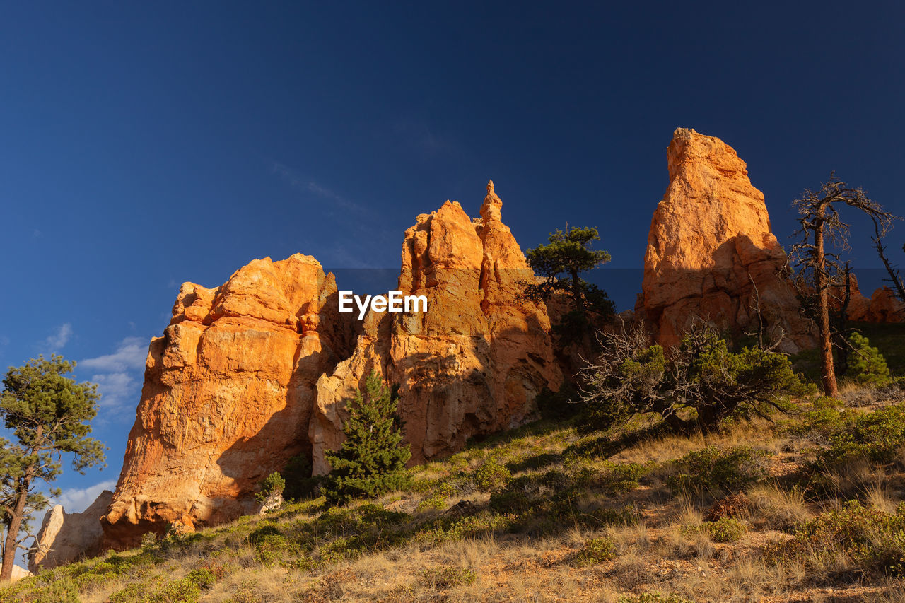 rock, sky, rock formation, rock - object, beauty in nature, scenics - nature, solid, non-urban scene, tranquil scene, physical geography, nature, no people, tranquility, environment, geology, plant, blue, sunlight, landscape, land, outdoors, formation, eroded, arid climate, climate, mountain peak