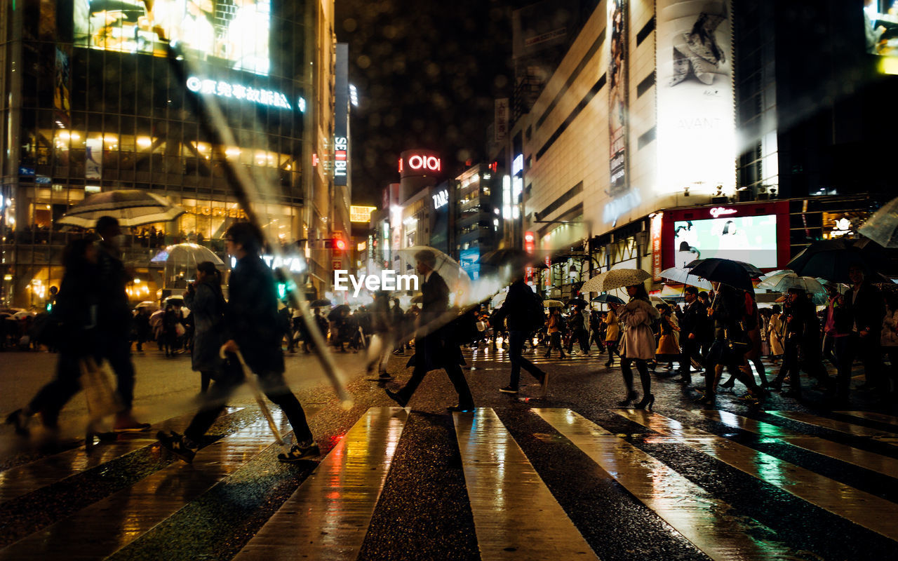 large group of people, illuminated, night, street, building exterior, architecture, built structure, city, walking, real people, city street, city life, men, outdoors, road, women, crowd, people