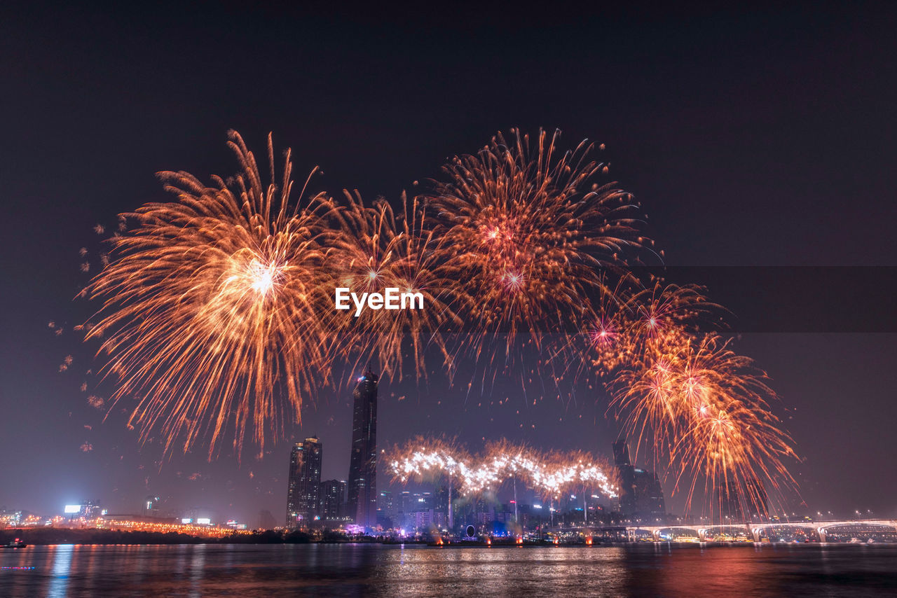 night, firework display, illuminated, firework - man made object, long exposure, celebration, exploding, arts culture and entertainment, blurred motion, event, waterfront, water, sky, river, motion, firework, outdoors, low angle view, multi colored, no people, clear sky