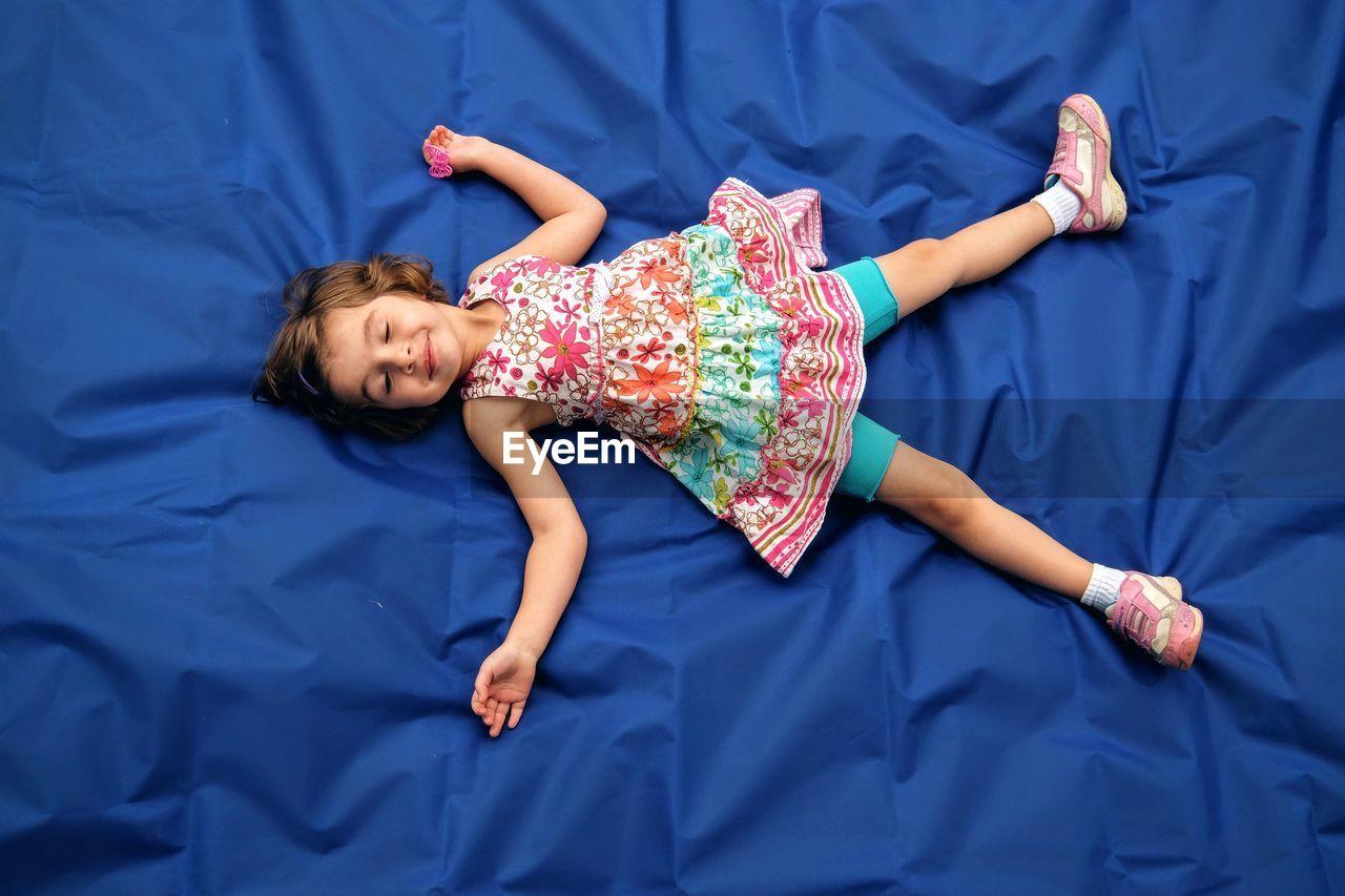 Full Length Of Cute Girl Sleeping On Blue Fabric In Yard