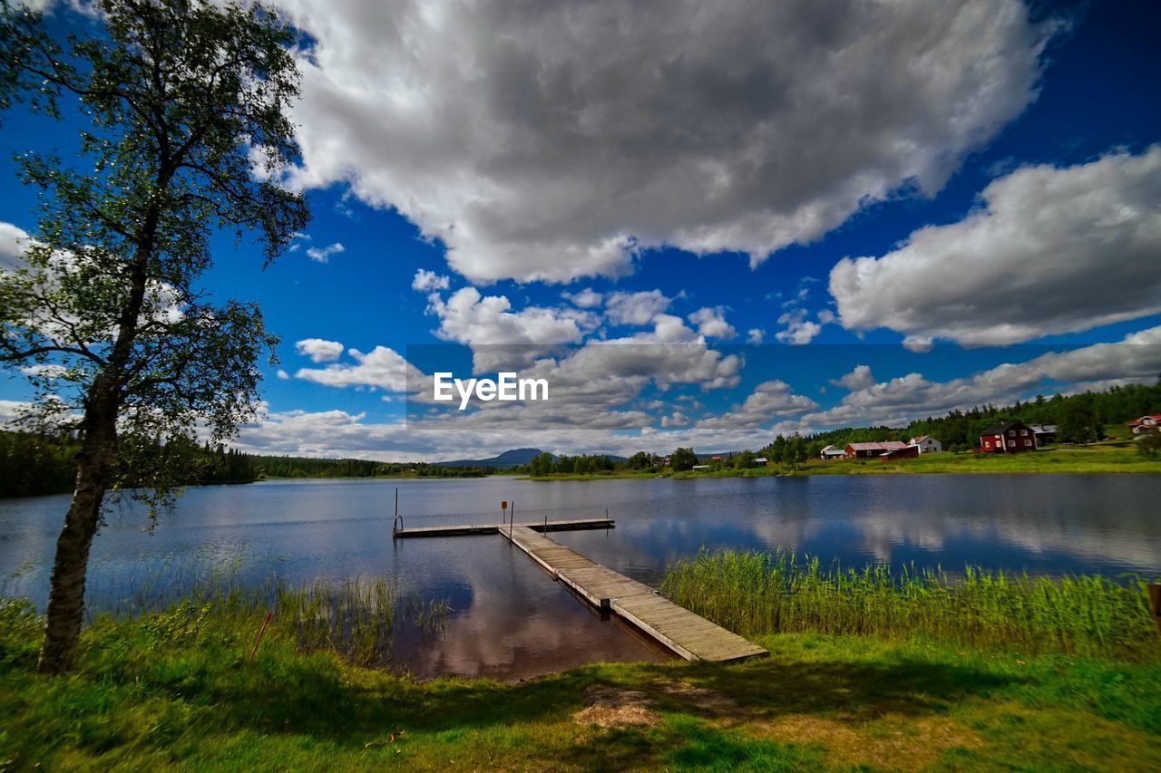 water, lake, cloud - sky, tranquility, beauty in nature, sky, nature, tranquil scene, scenics, reflection, no people, non-urban scene, outdoors, day, tree, green color, grass, landscape