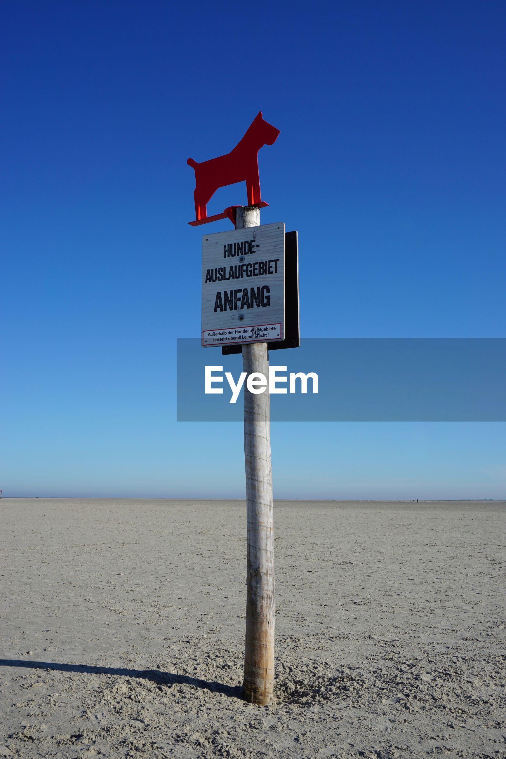 Information sign on beach against clear blue sky