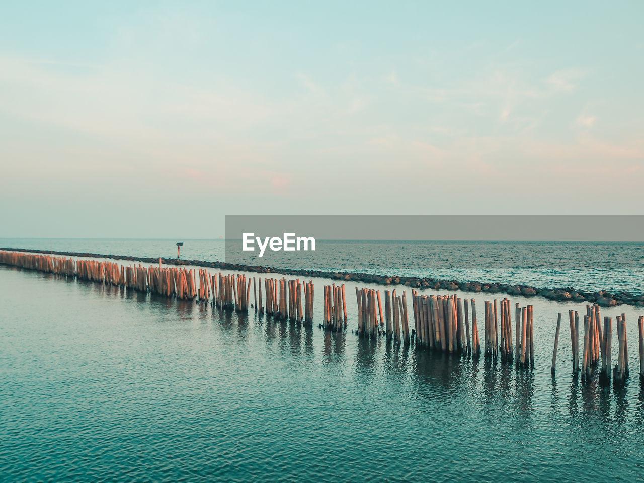 water, sea, horizon over water, sky, horizon, scenics - nature, beauty in nature, tranquility, tranquil scene, waterfront, nature, cloud - sky, no people, sunset, idyllic, beach, non-urban scene, land, outdoors, wooden post, groyne