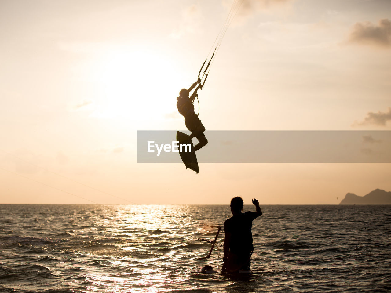 Rear View Of Silhouette Man Looking At Kitesurfer Above Sea At Sunset