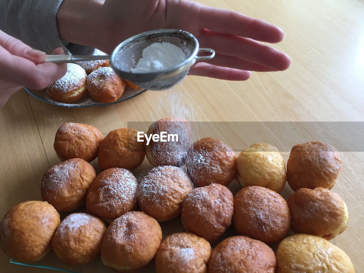 Cropped Image Of Hand Dusting Powdered Sugar On Donuts