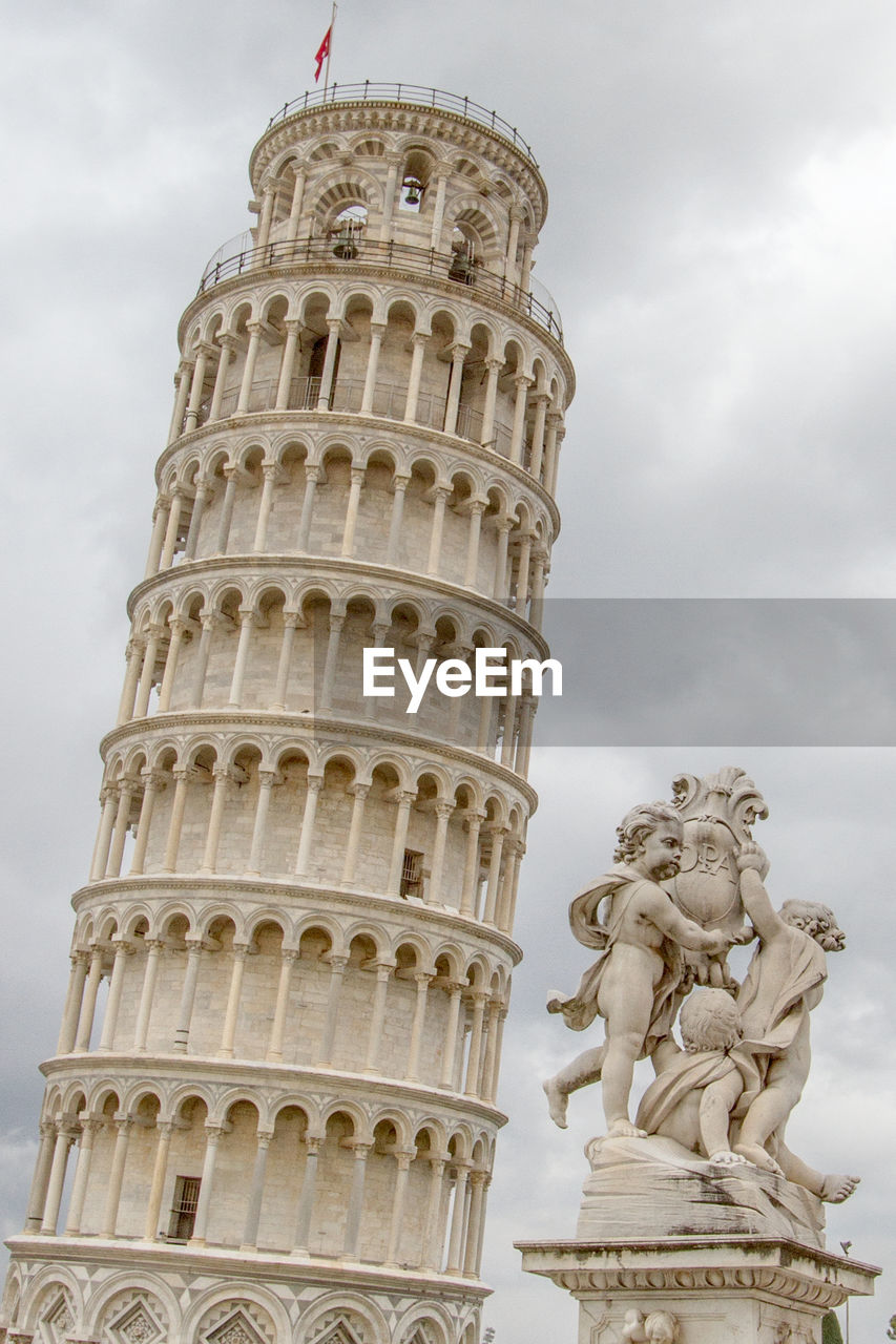 Leaning Tower Of Pisa And Statue Against Sky