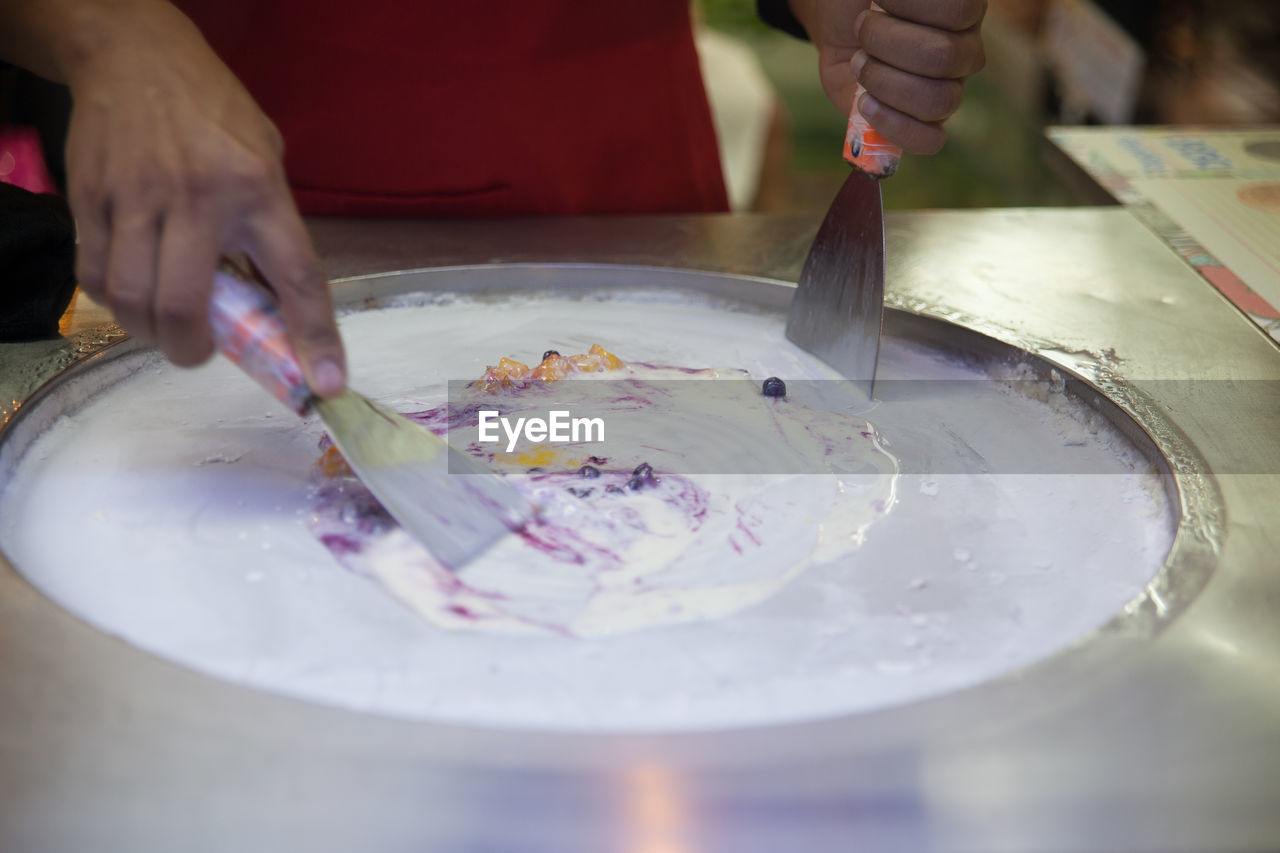 Midsection of man making ice cream rolls in kitchen