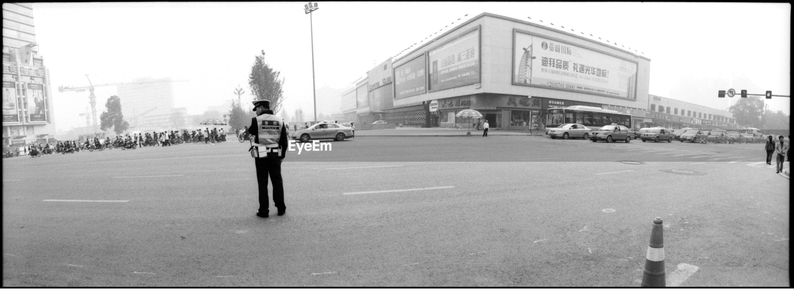 Rear view of a traffic police standing on road