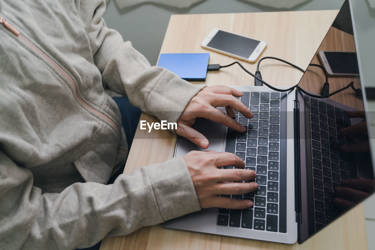 MIDSECTION OF MAN WORKING WITH LAPTOP