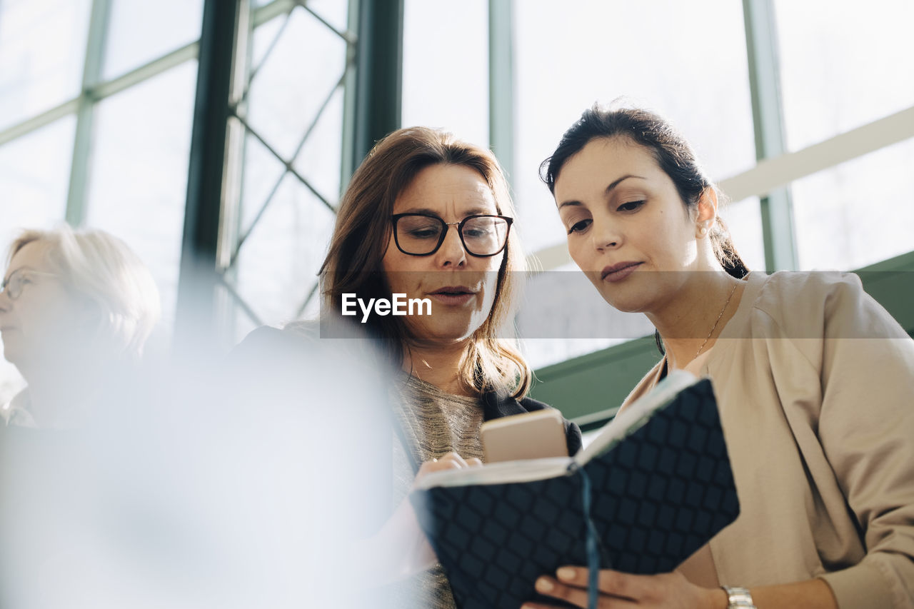 communication, young adult, adult, women, young women, indoors, colleague, office, working, coworker, cooperation, real people, business person, glasses, eyeglasses, technology, business, businesswoman, teamwork, wireless technology