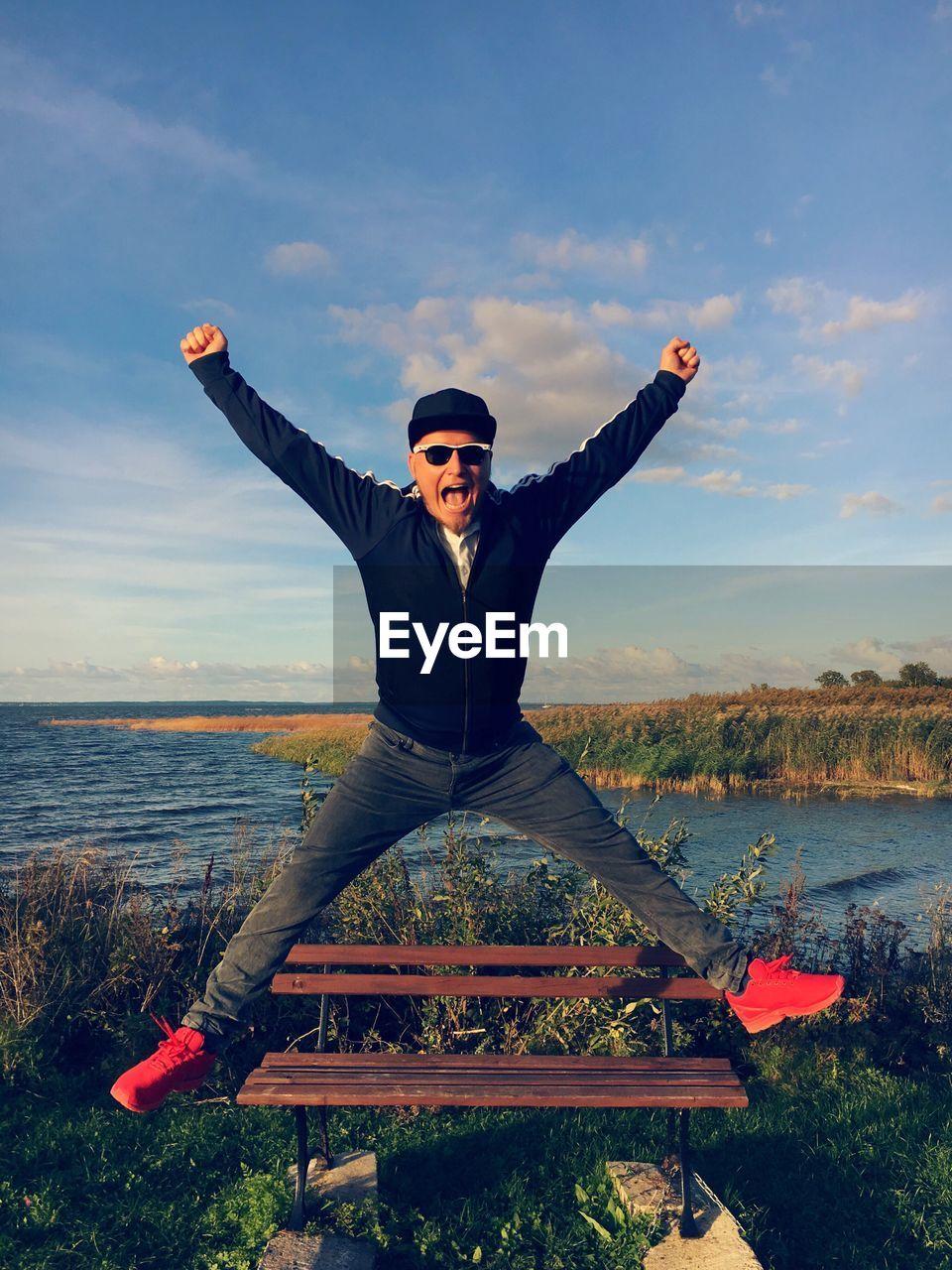 Full Length Portrait Of Happy Man Jumping Against Lake