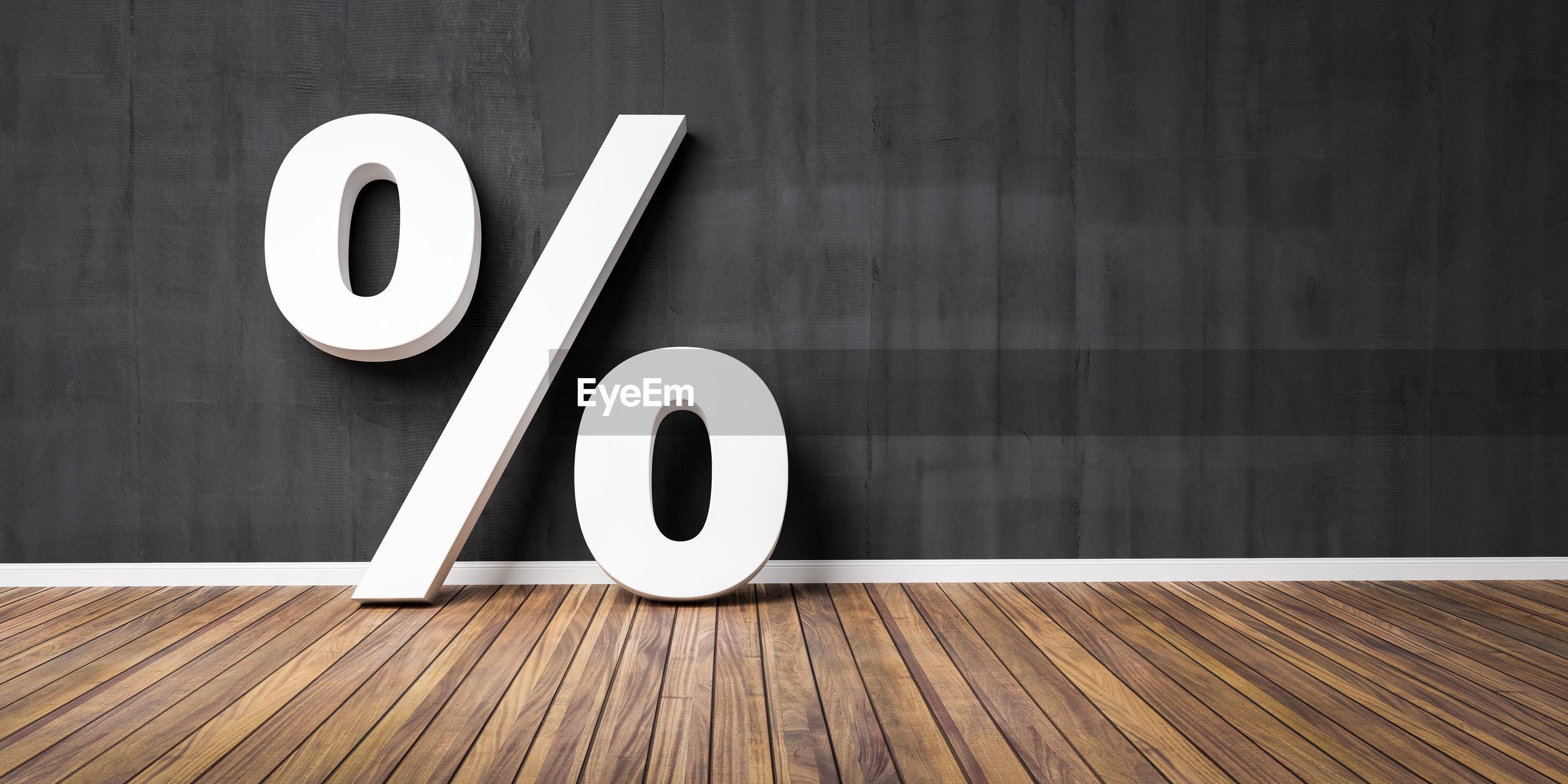 Large percentage sign on hardwood floor