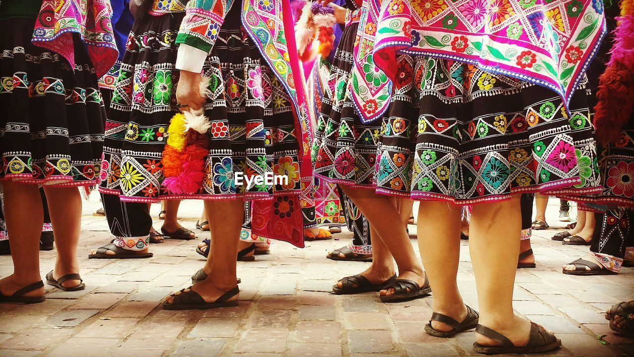 Low section of women wearing colorful skirts standing on street