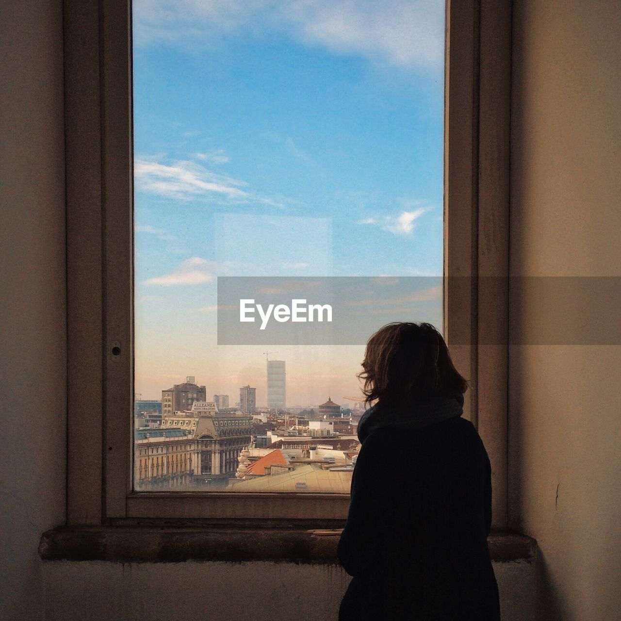Rear View Of Woman Looking At View Of Cityscape Through Winow