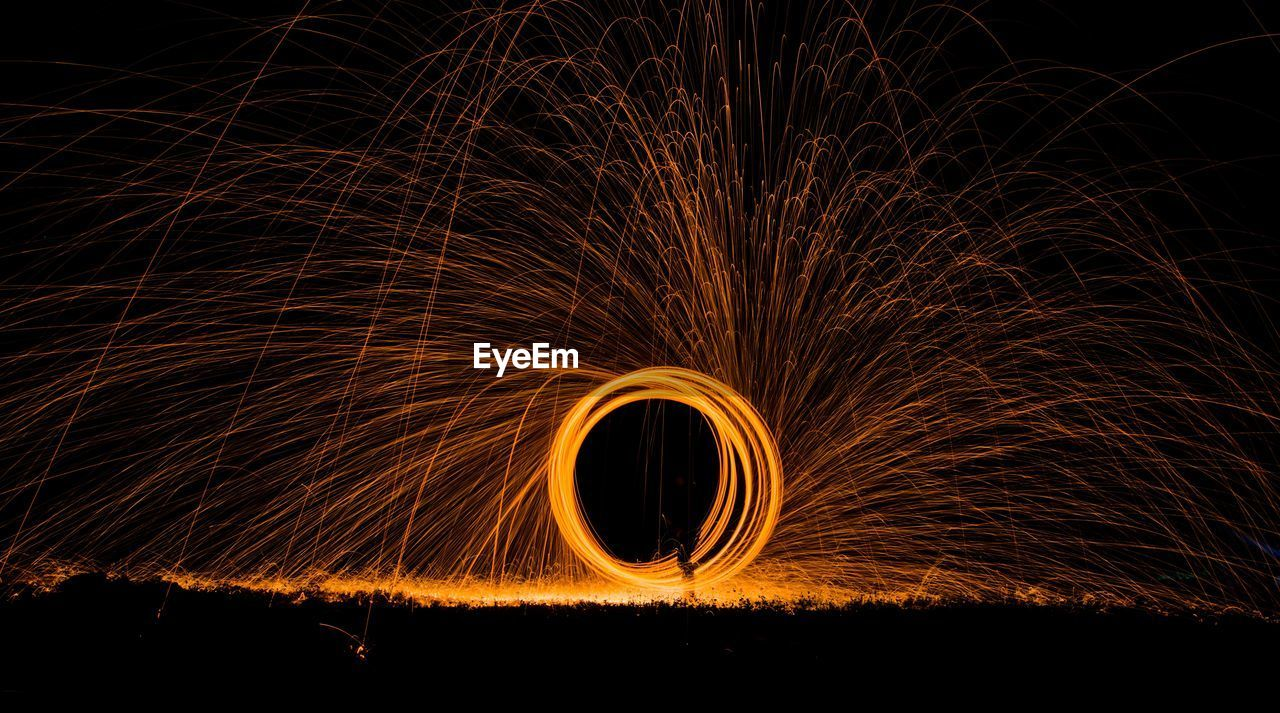 motion, night, wire wool, spinning, illuminated, blurred motion, long exposure, burning, glowing, fire, sparks, sign, fire - natural phenomenon, orange color, nature, warning sign, one person, circle, light painting, geometric shape, outdoors, dark, light