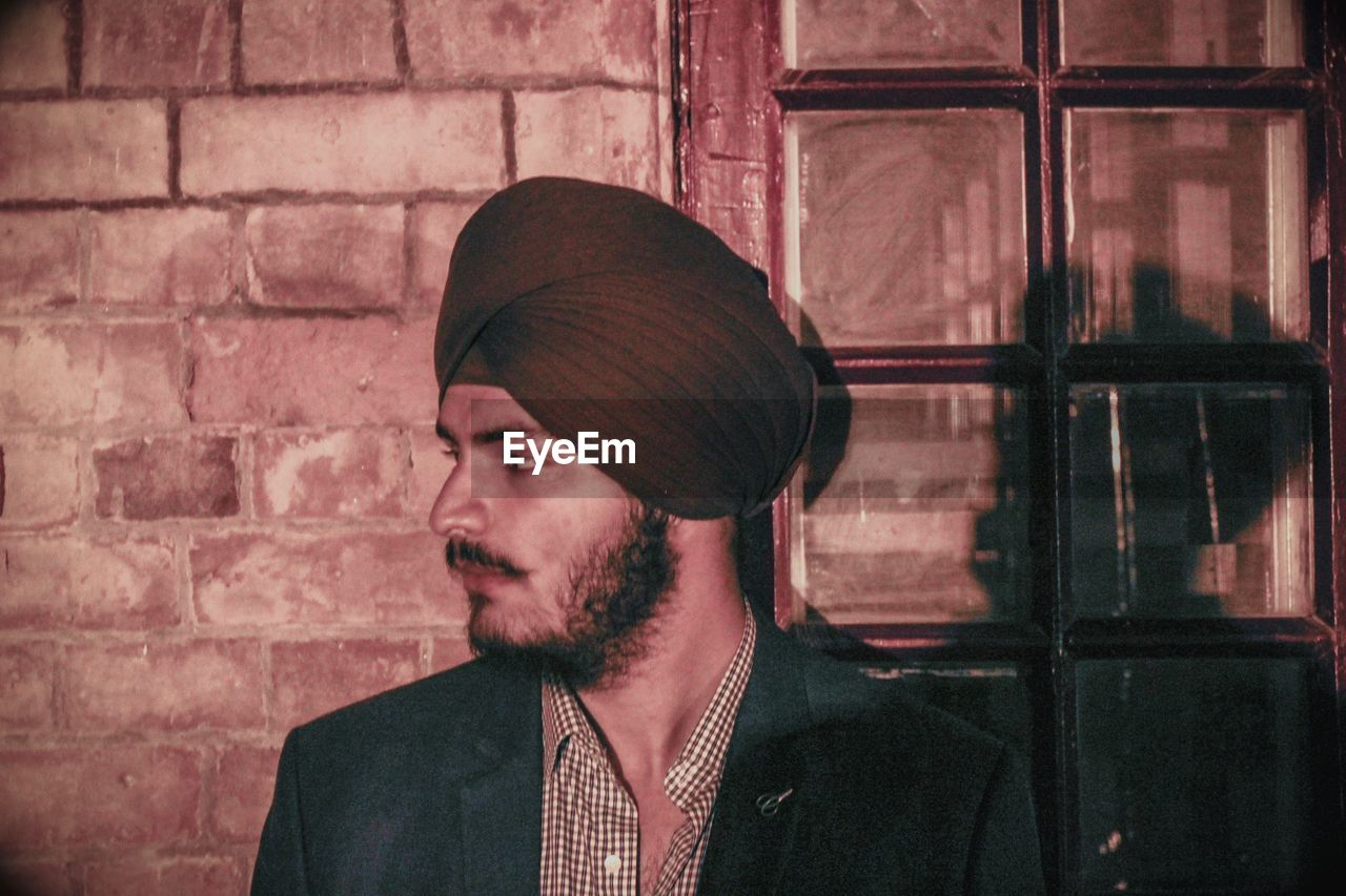 Thoughtful man wearing turban while standing against brick wall