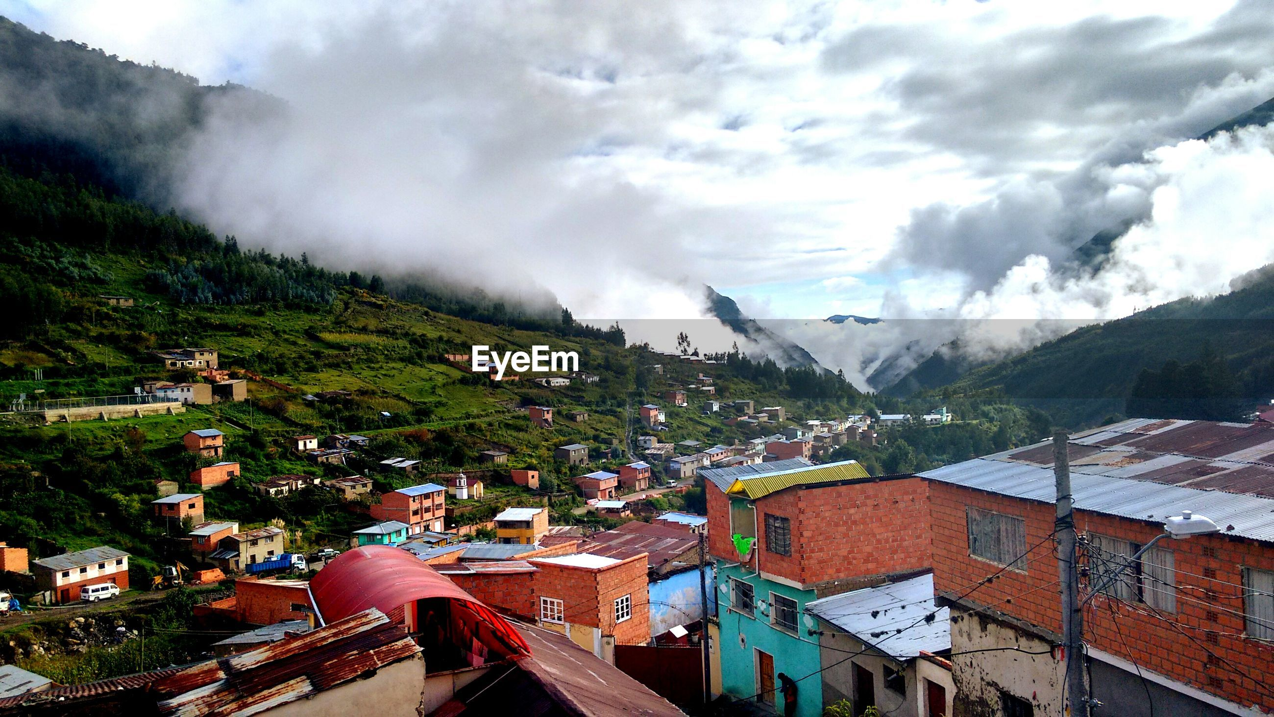 mountain, building exterior, architecture, built structure, sky, mountain range, cloud - sky, high angle view, tree, residential building, residential district, house, residential structure, cloudy, weather, city, scenics, landscape, nature, cloud
