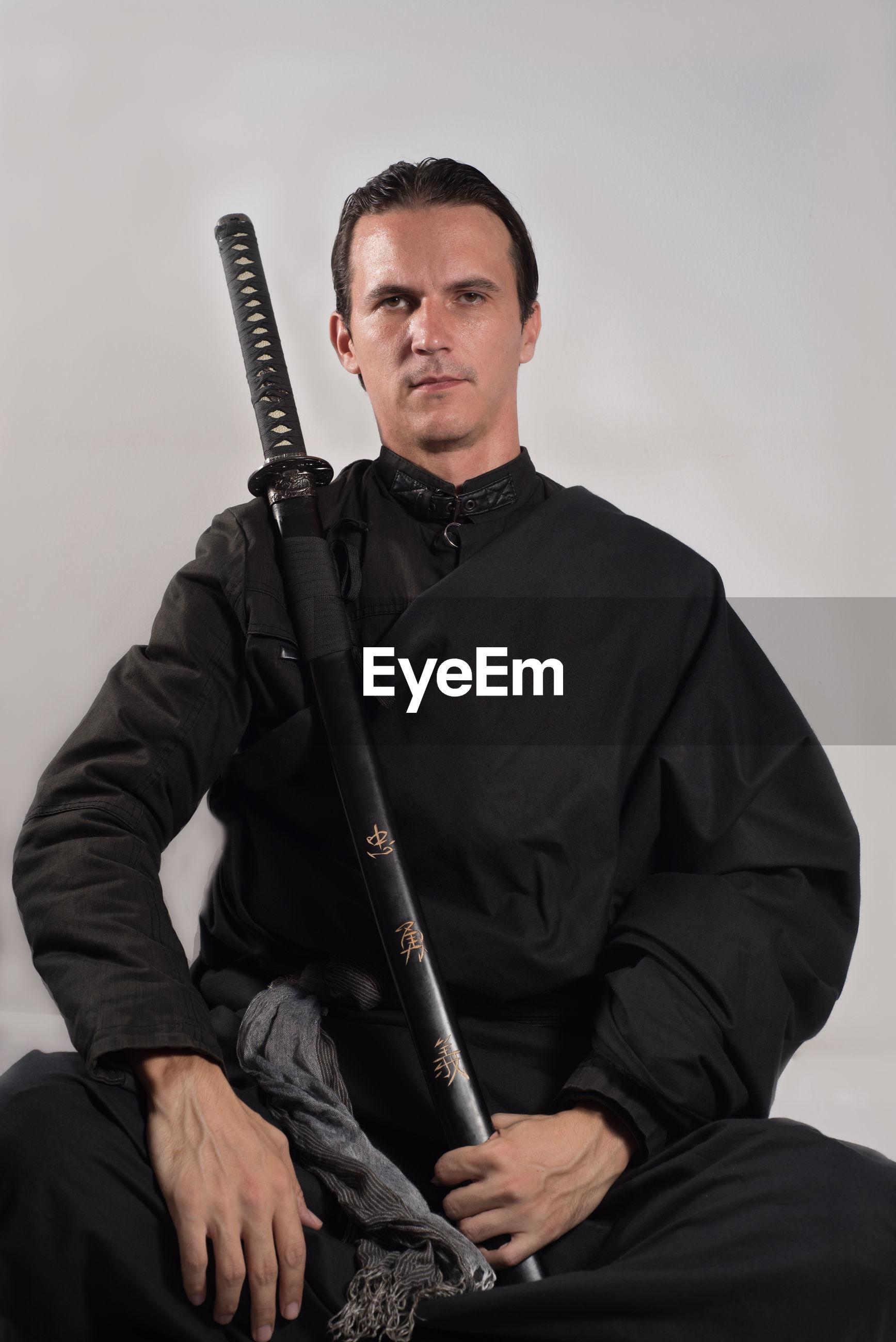Portrait of serious samurai with katana sitting against gray background